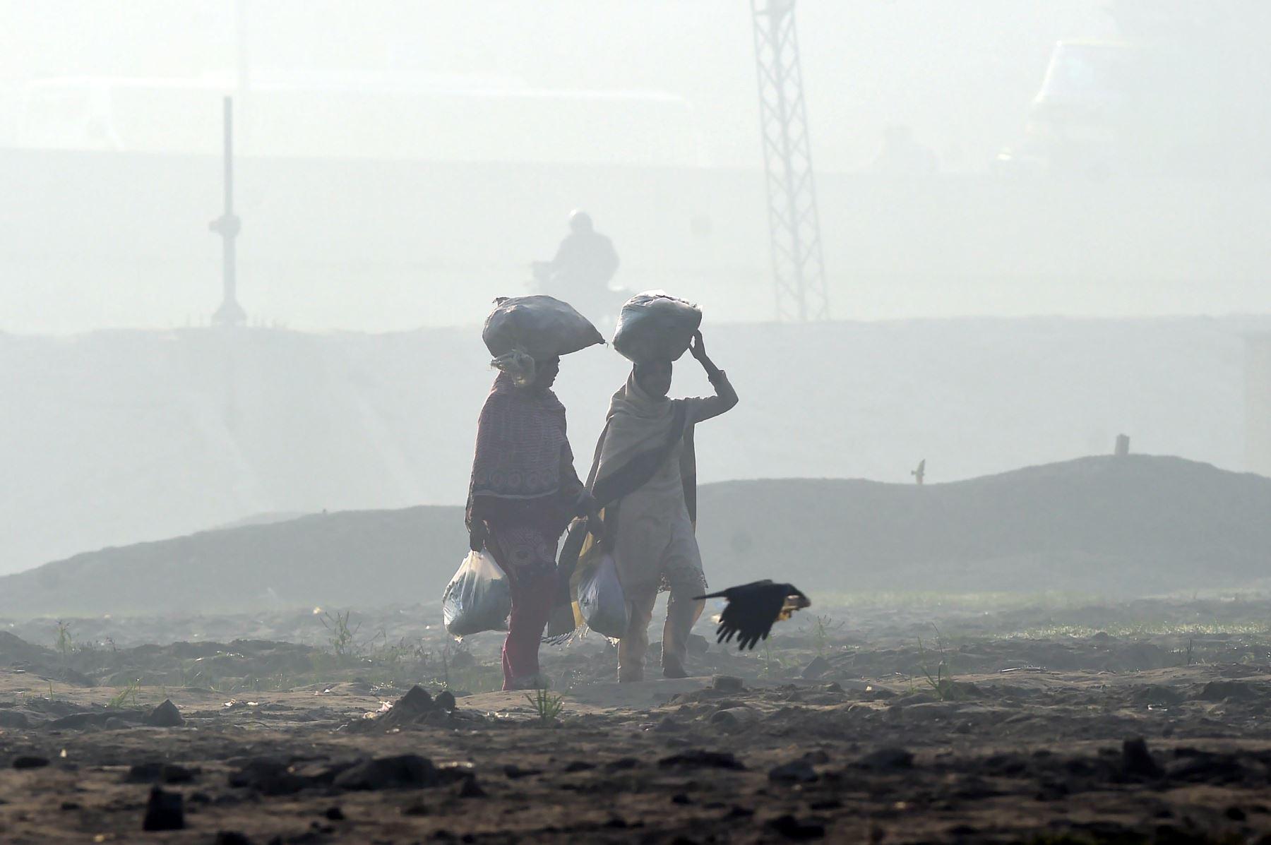 Pakistaní lleva sus pertenencias en medio de la niebla en Lahore.AFP