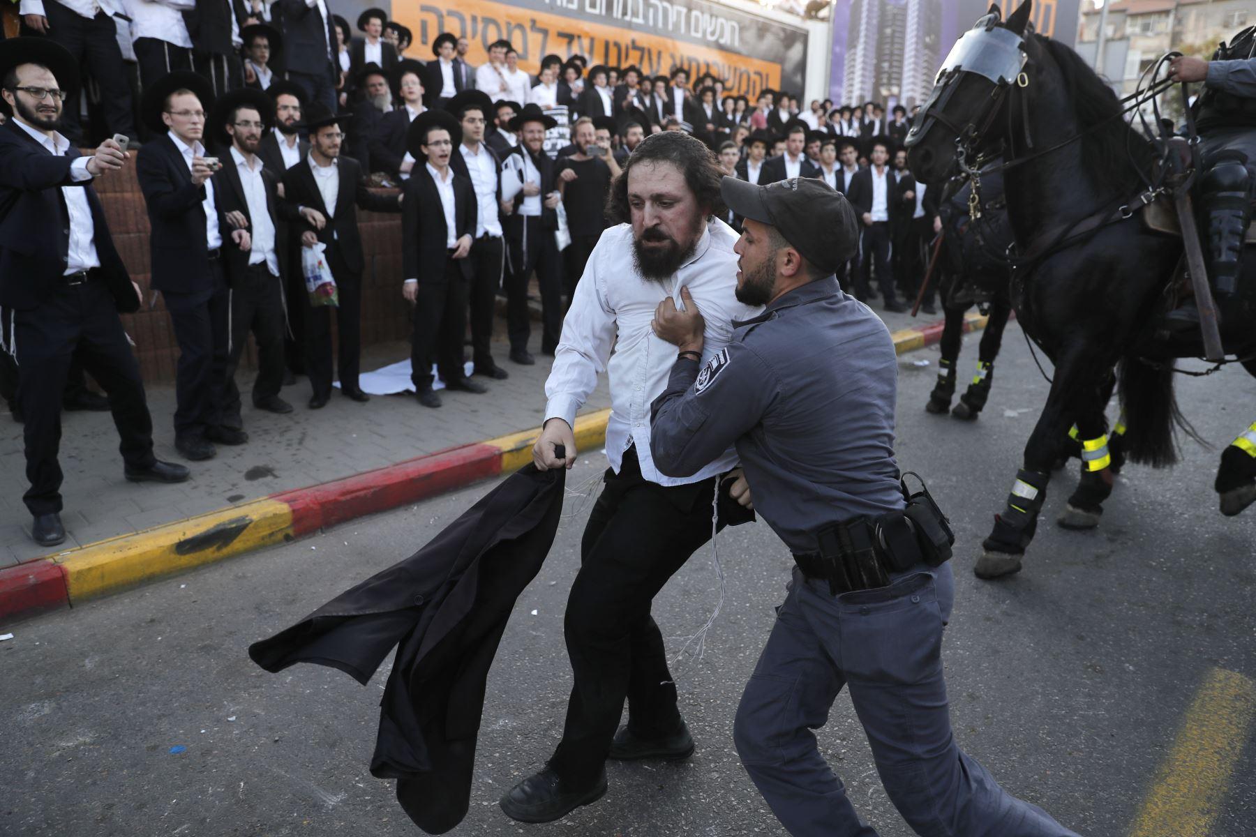Policias israelíes se llevan  manifestante judío ultra ortodoxo que manifestaba contra el servicio militar israelí en  Tel Aviv. AFP