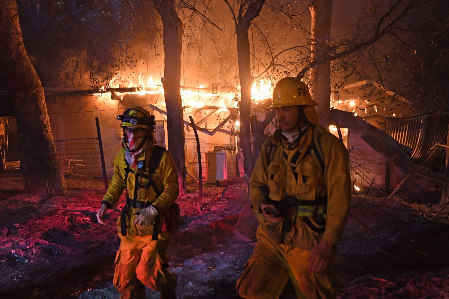 Bomberos se alejan de una casa en llamas en California. Foto: AFP