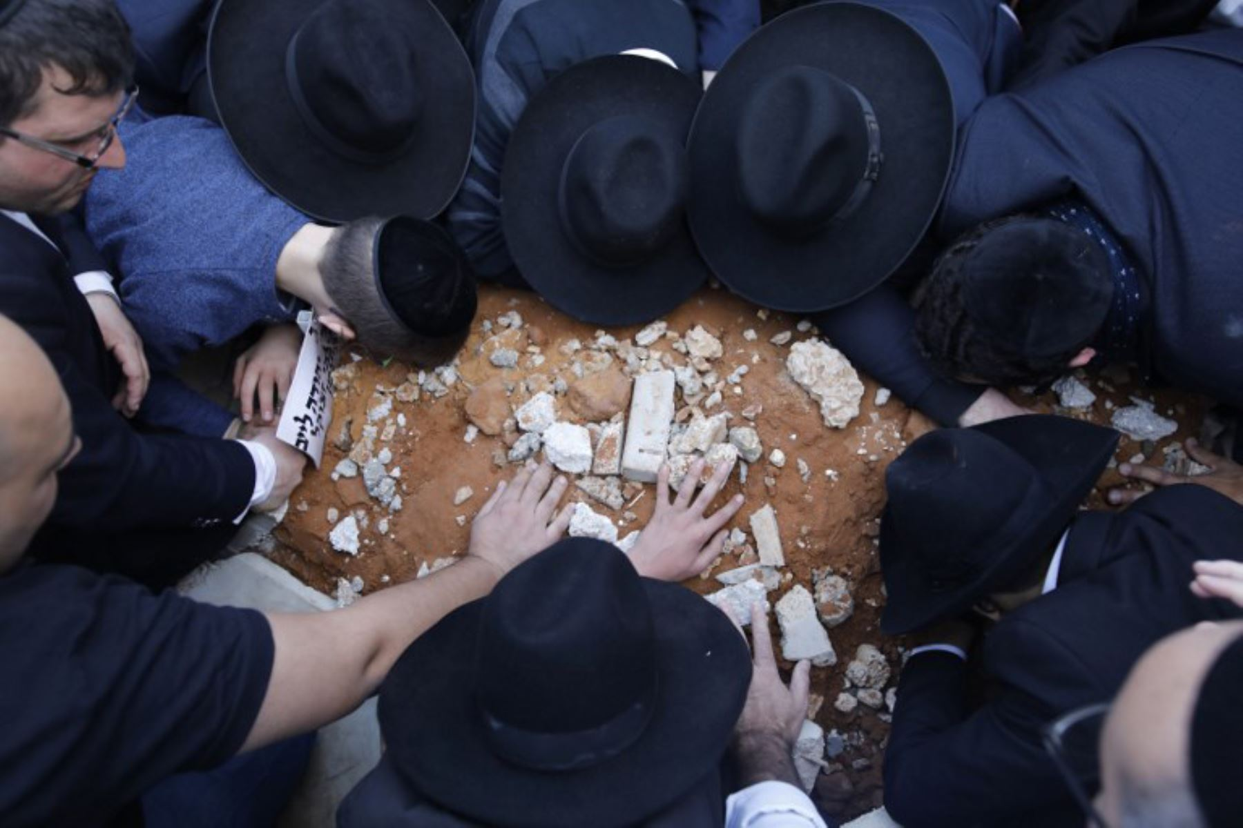 Judíos ultraortodoxos tocan y besan la tumba del rabino Aaron Yehuda Leib Shteinman, durante su funeral en Israel. Foto: AFP