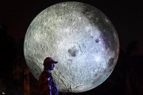 Visitantes indios observan una instalación que representa a la luna iluminada.