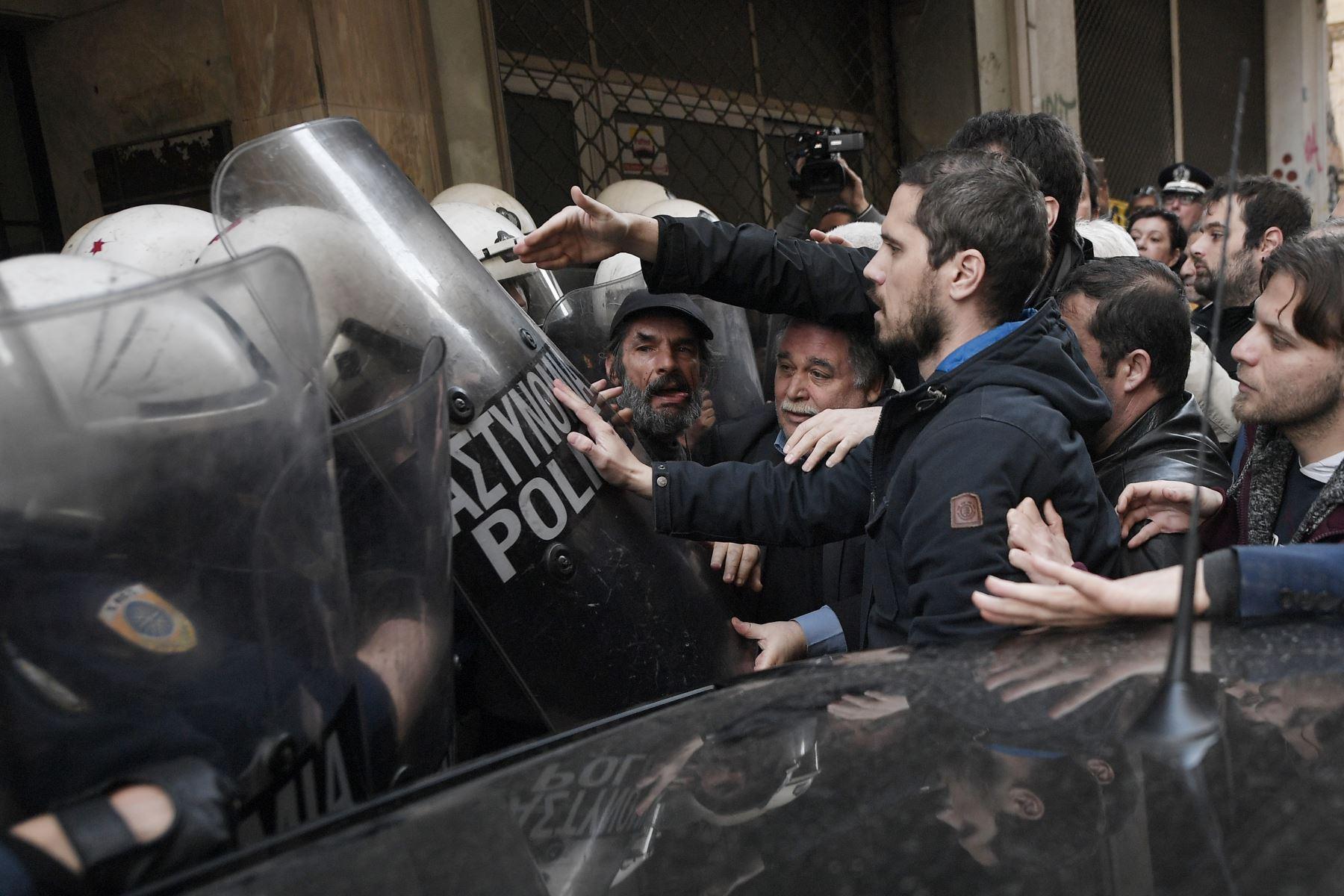 Manifestantes intentan detener una subasta de bienes en la entrada de una notaria en Atenas.Foto: AFP