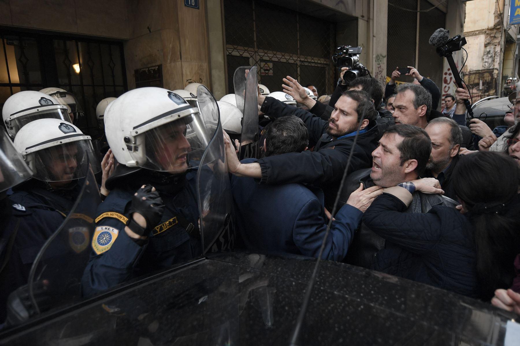 Manifestantes se enfrentan con la policía que custodia la entrada de una notaría pública en Atenas. Foto: AFP
