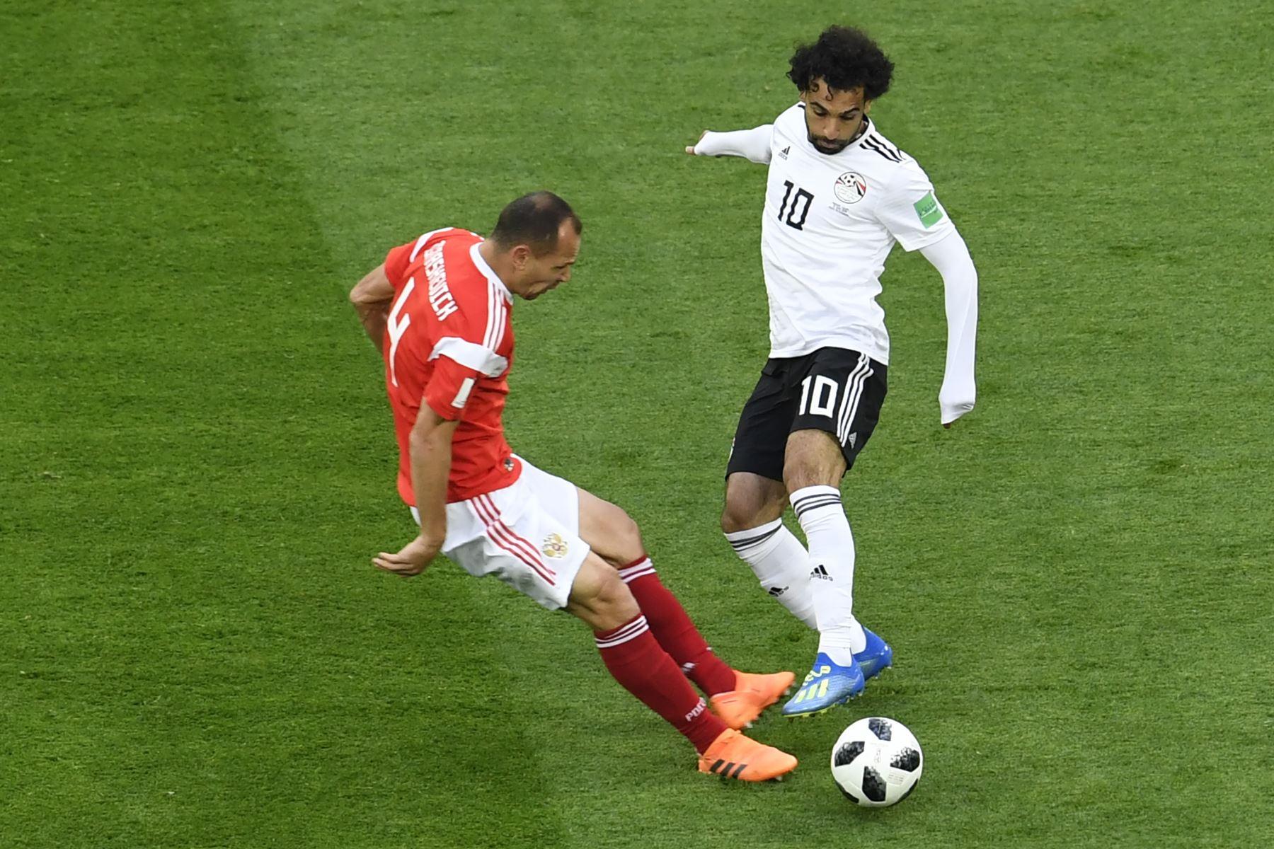 El delantero egipcio Mohamed Salah (R) regatea al defensor ruso Sergey Ignashevich durante el partido de fútbol del Grupo A de la Copa Mundial Rusia 2018 entre Rusia y Egipto en el estadio San Petersburgo de San Petersburgo el 19 de junio de 2018. / AFP