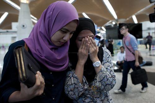 Familiares del vuelo MH17 a las afueras del aeropuerto internacional de Malasia. AFP