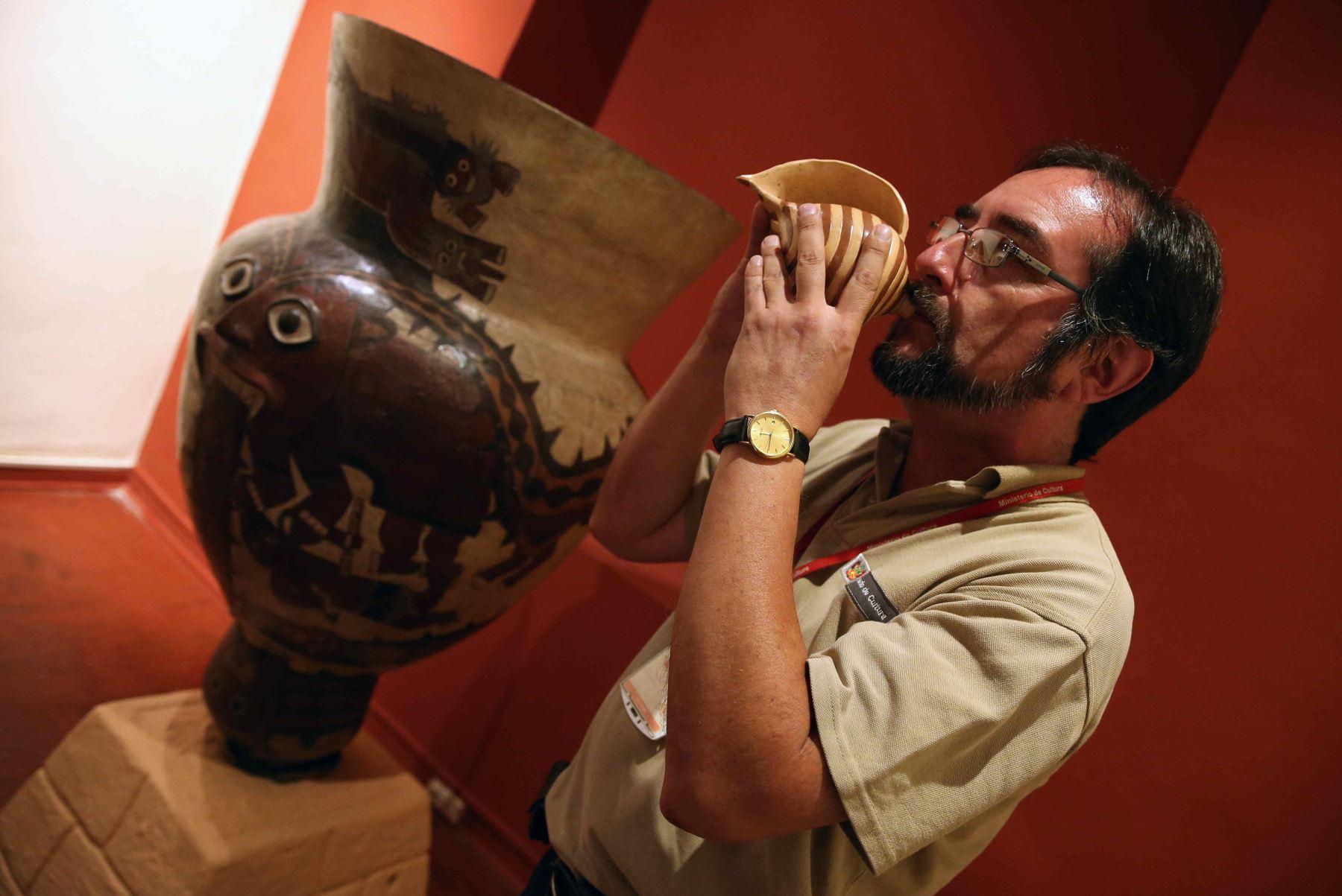 Investigador musical, Milano Trejo tocando un cerámica con forma de pututo en la exposición de la muestra Sonidos del Ande. Foto: EFE