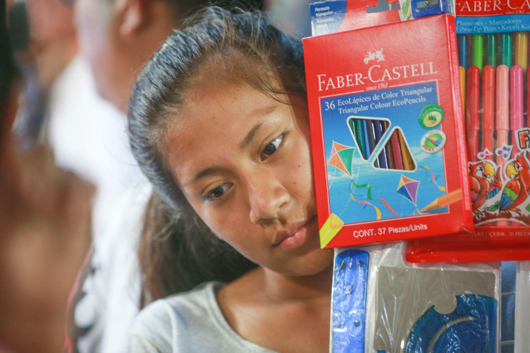 Una estudiante adolescente observa la trajinada visita de su madre en el Mercado Central en busca de los precios más baratos. Foto: ANDINA/ Jhony Laurente