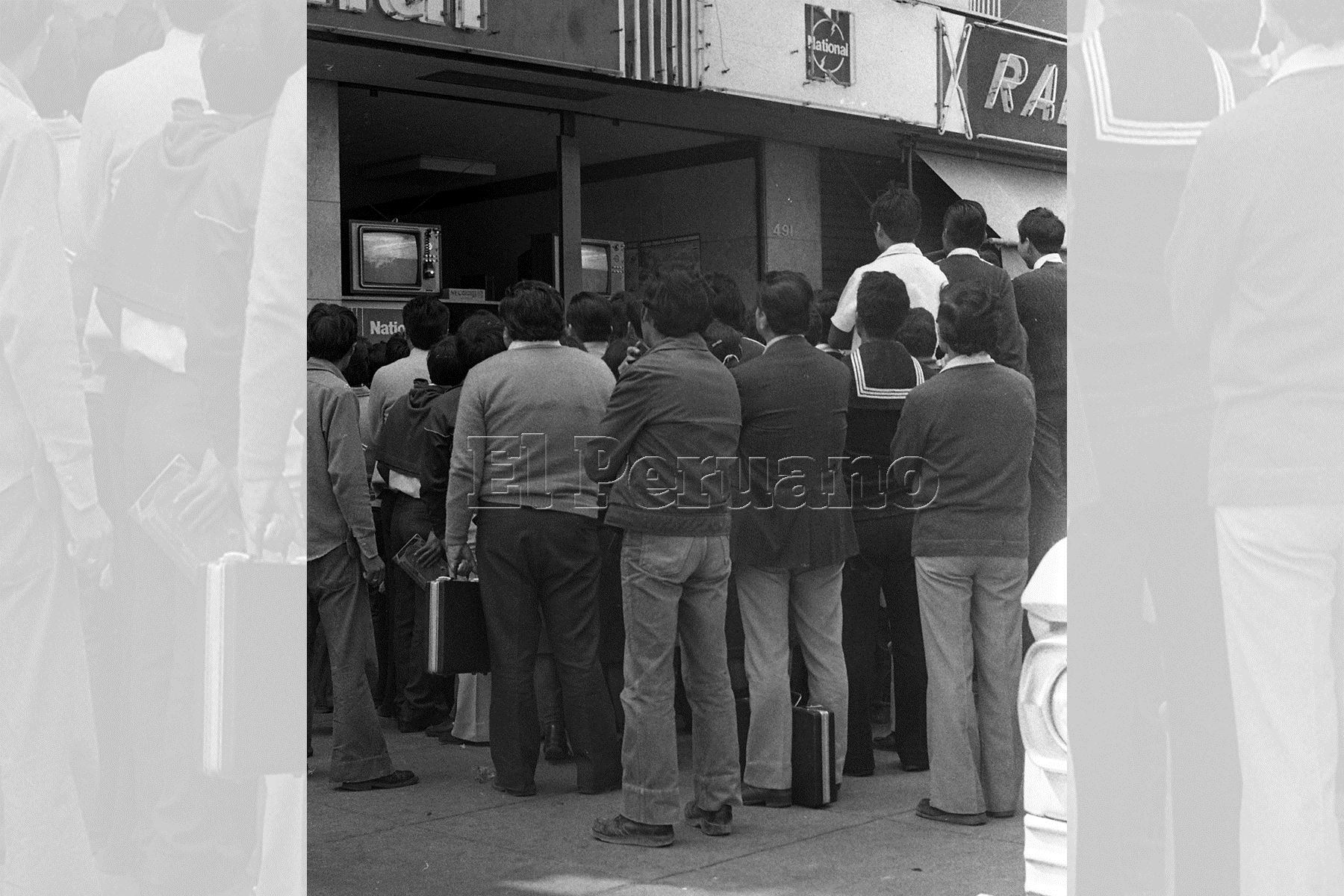 Frente a una tienda comercial un grupo de personas sigue las incidencias del partido entre Perú y Camerún en el Mundial España 82.  Foto:ANDINA/archivo
