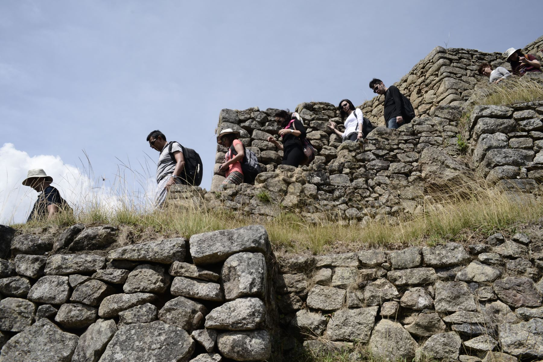Esta foto tomada el 27 de agosto de 2016 muestra a los visitantes admirando las ruinas de Machu Picchu, que se encuentra a 2,430 metros sobre el nivel del mar. Incrustado en un paisaje espectacular en el punto de encuentro entre los Andes peruanos y la cuenca del Amazonas, el Santuario Histórico de Machu Picchu es uno de los mayores logros artísticos, arquitectónicos y de uso de la tierra en cualquier lugar y el legado tangible más significativo de la civilización Inca.  Foto: AFP