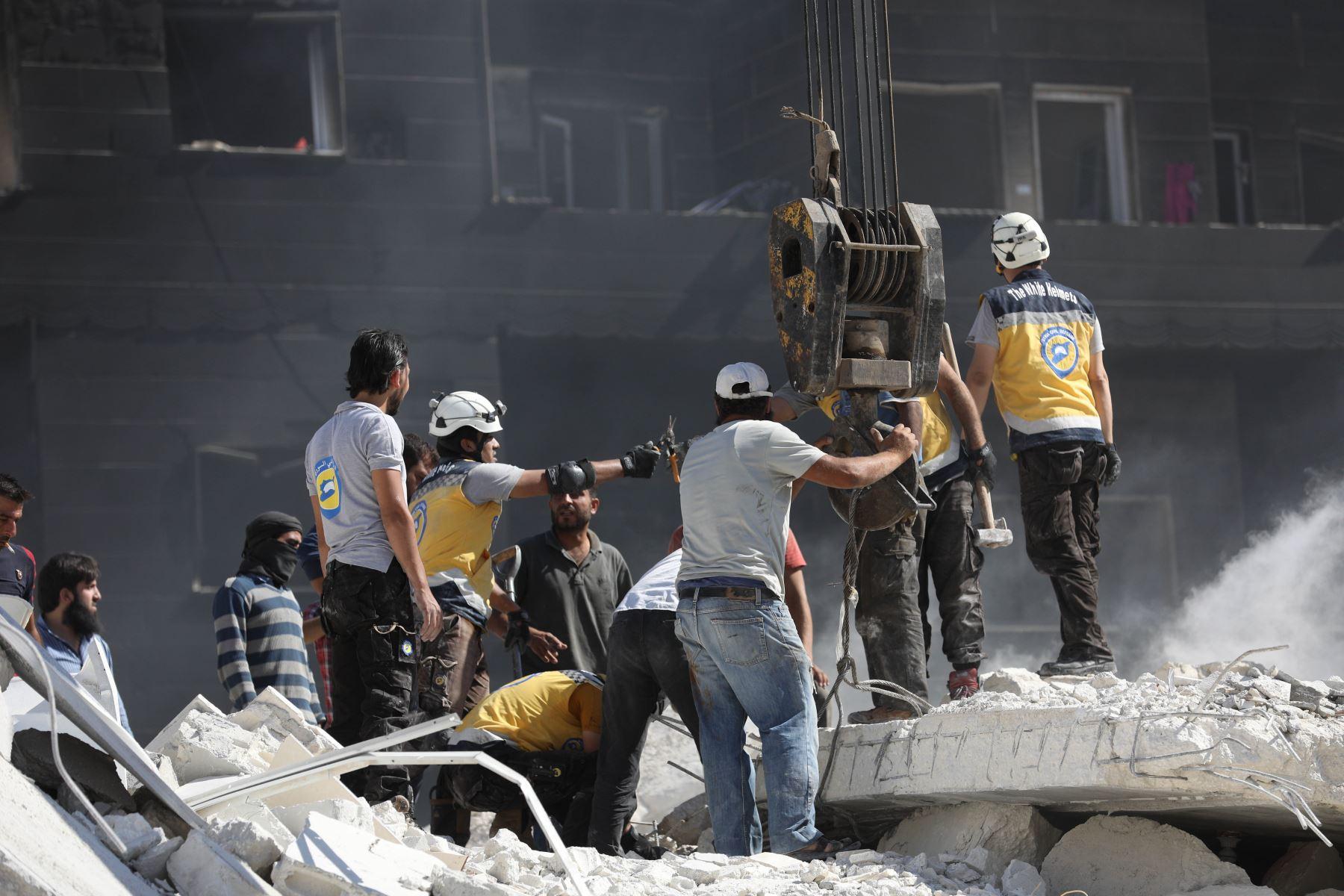 El personal de rescate, conocido como White Helmets revisa los escombros de los edificios destruidos, tras una explosión en un depósito de armas en una zona residencial en la ciudad de Sarmada en la norteña Siria de Idlib, en la que docenas de personas supuestamente asesinado. / AFP