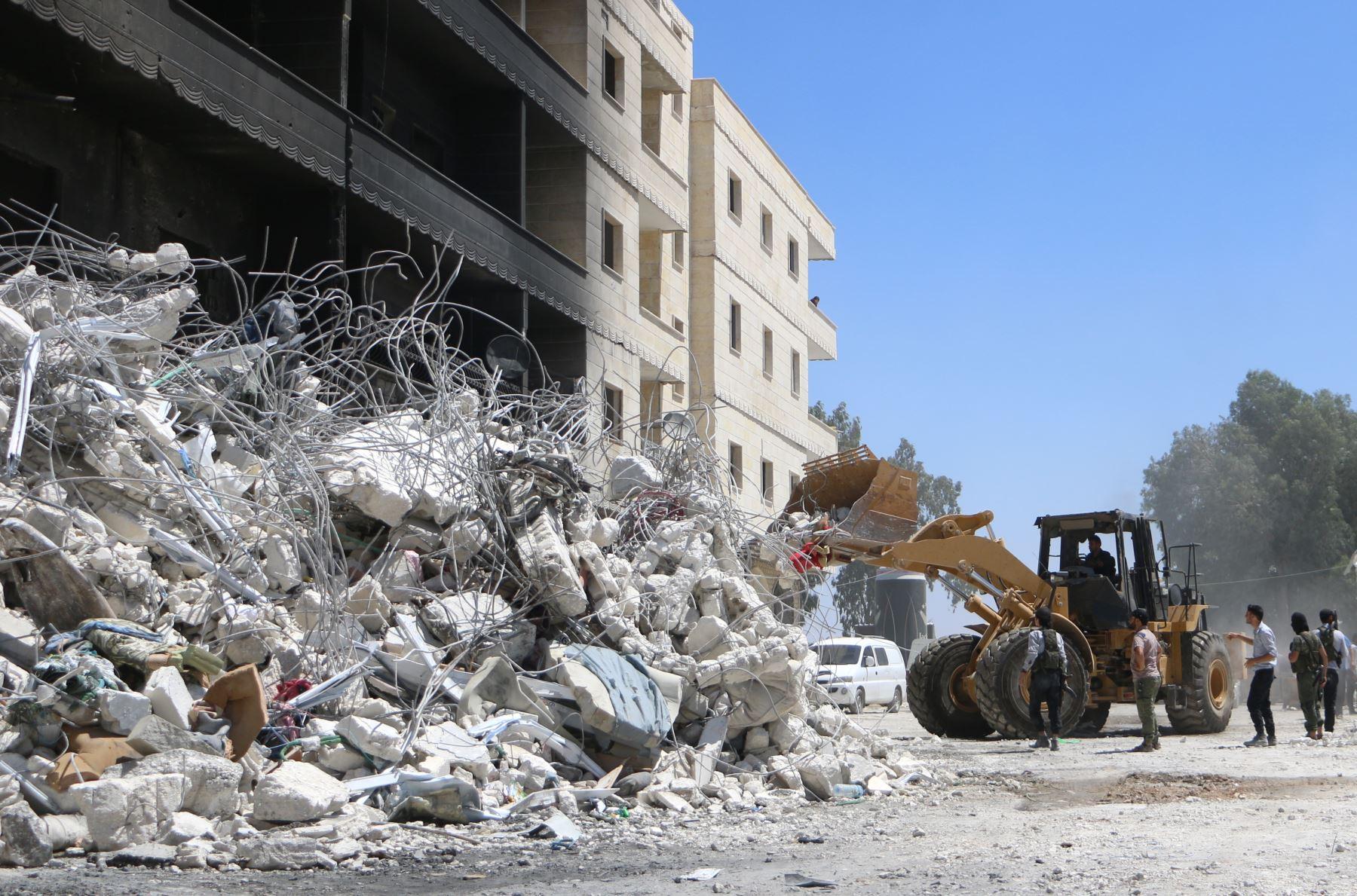 Un tractor limpia los escombros de los edificios destruidos el 13 de agosto de 2018 después de una explosión en un depósito de armas en una zona residencial en la ciudad de Sarmada en la norteña Siria de Idlib en la que decenas de personas murieron. / AFP