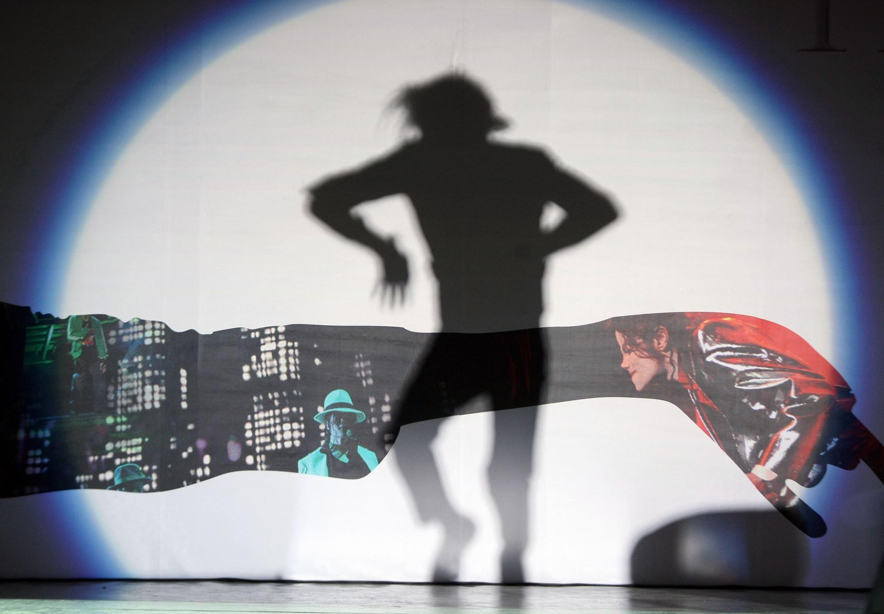 La sombra de un imitador de Michael Jackson de China es interpretada por miles de admiradores reunidos afuera del Cine Saga en Beijing. Foto: AFP