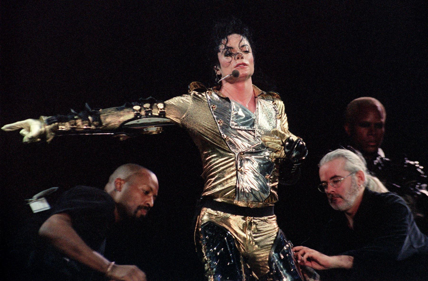 El actor y estrella del pop estadounidense Michael Jackson recibe ayuda de su equipo, quitándose su traje espacial el 25 de octubre de 1996 en Singapur. Foto: AFP