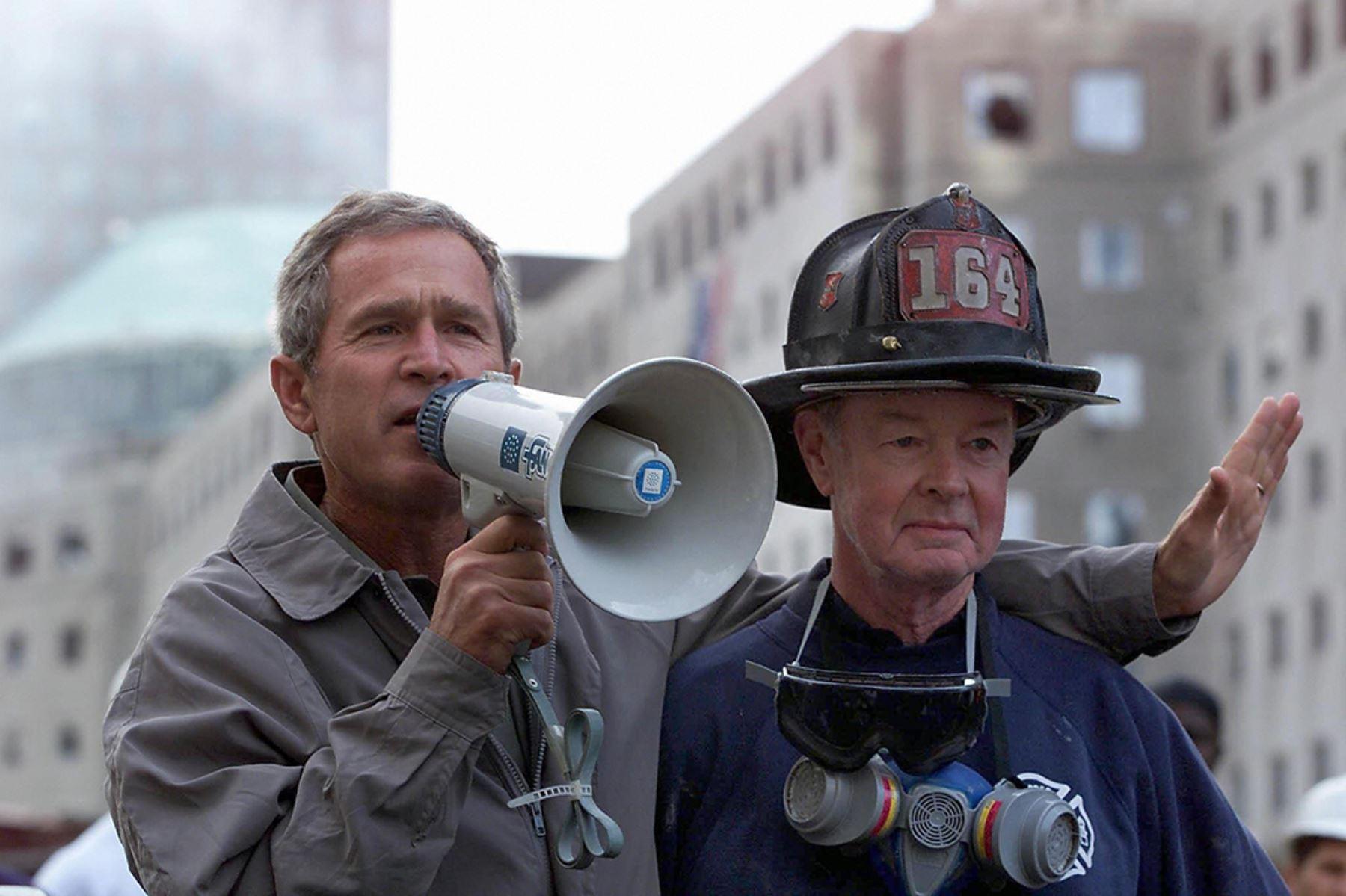 El presidente estadounidense George W. Bush (L), junto al bombero jubilado Bob Beckwith, de 69 años, habla con voluntarios y bomberos mientras examina el daño en el sitio del World Trade Center en Nueva York el de septiembre de 2001. Foto: AFP