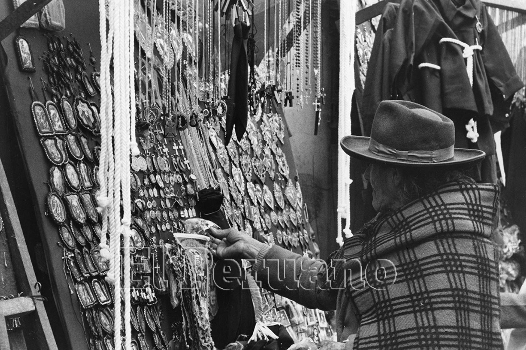 Lima - 4 Octubre 1976 / Una anciana observa los detentes o escapularios que  comercializan los ambulantes en las inmediaciones de la Iglesia las Nazarenas en el mes del Señor de los Milagros. Foto: Archivo Histórico de EL PERUANO / Rolando Ángeles