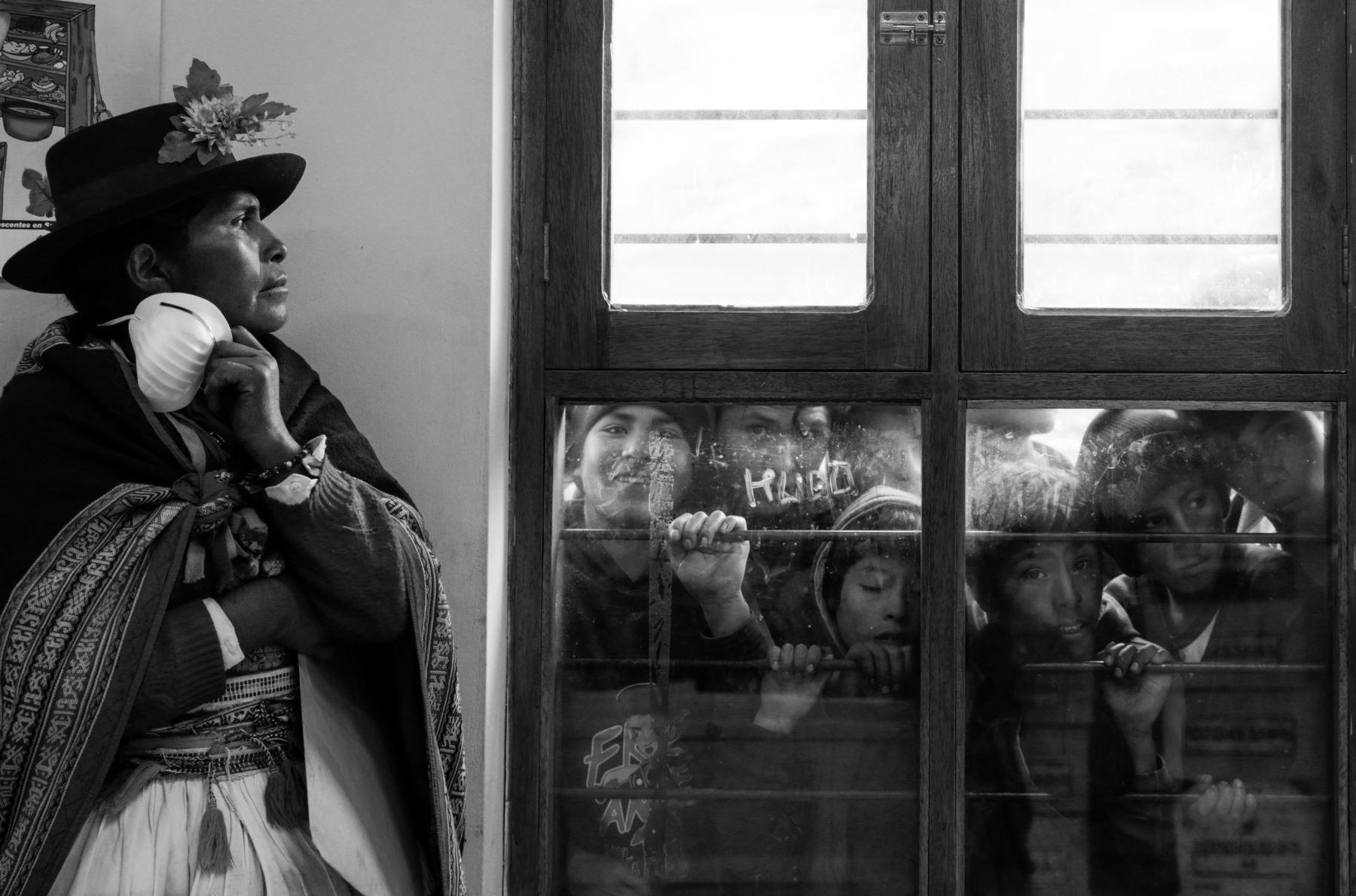 Una pobladora de Llaccua (Ayacucho) espera en el frío pasillo de la posta medica la entrega de los restos de su familiar. A través de la ventana, la curiosidad de los niños se asoma. Foto: ANDINA/Jack Ramón