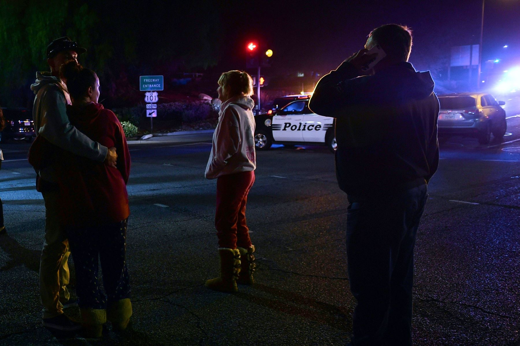 Las personas se ponen de pie y observan cómo se despliega la escena desde la intersección de la autopista US 101 y la salida de Moorpark Rad mientras los vehículos de la policía cierran el área frente a un bar de música country y salón de baile en Thousand Oaks, al oeste de Los Ángeles, donde un hombre armado abrió fuego tarde El 7 de noviembre de 2018, matando al menos a 12 personas, dijo la policía estadounidense. AFP