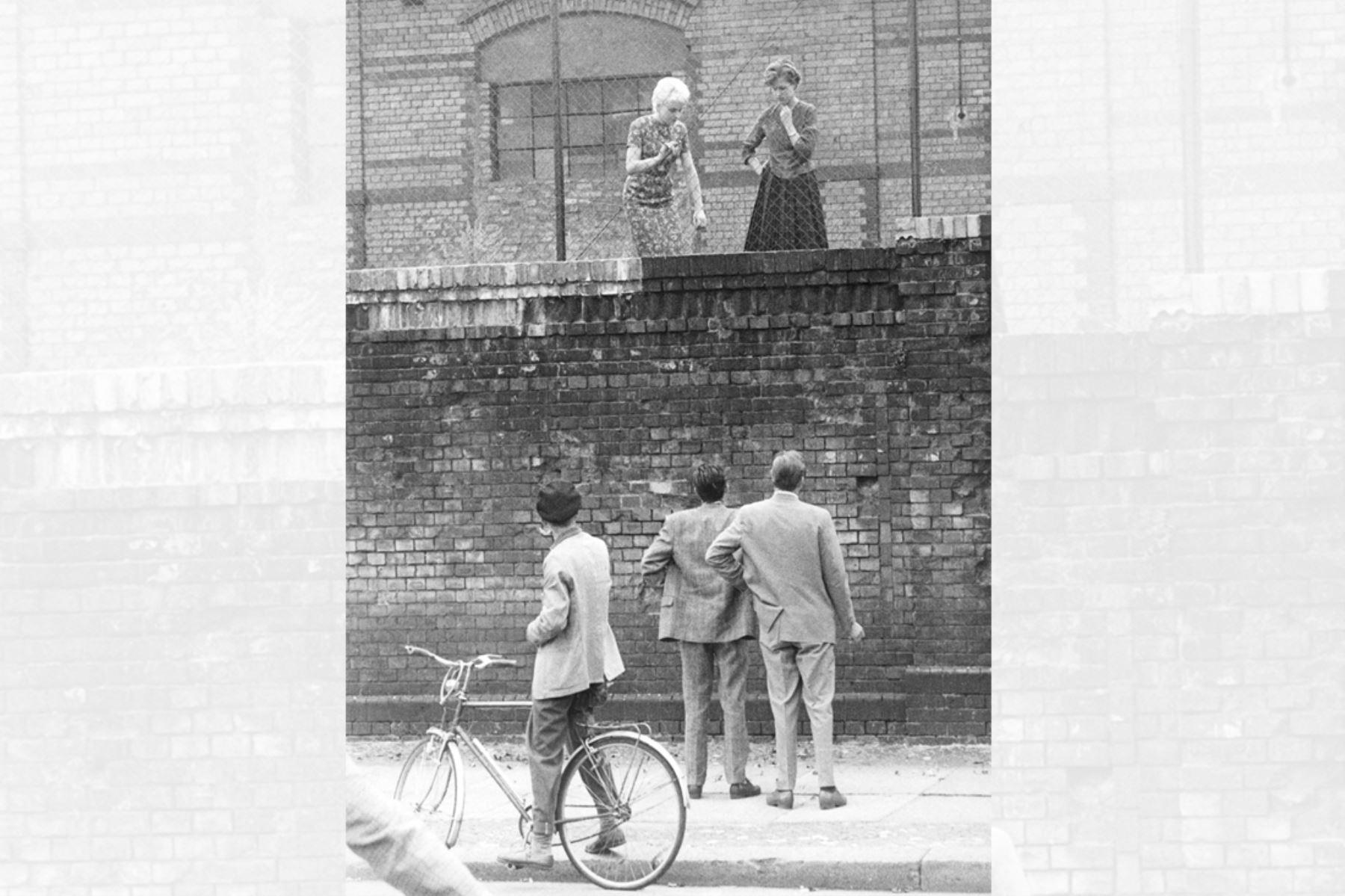Una imagen  tomada el 26 de agosto de 1961 muestra a dos hombres en el lado oeste del muro de Berlín conversando con sus amigas detrás de una cerca en la estación de tren Stettiner Bahnhof. Foto: AFP
