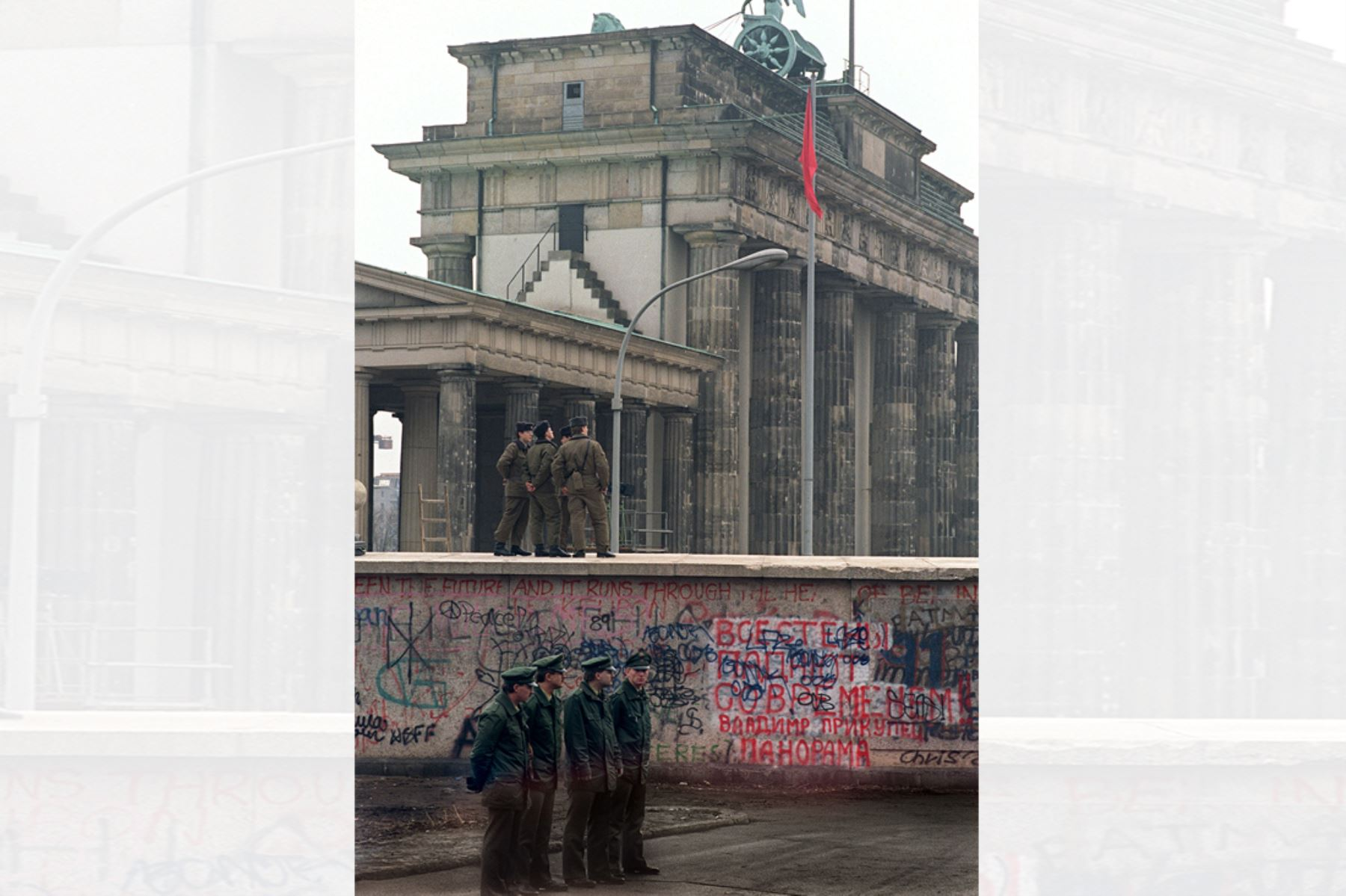 Policías  de Alemania Oriental y Alemania Occidental se encuentran cerca de la Puerta de Brandenburgo en Berlín el 22 de diciembre de 1989. El 9 de noviembre, Gunther Schabowski, portavoz del Partido Comunista de la RDA, declaró que a partir de la medianoche de ese día, los alemanes orientales serían libres de abandonar el país, sin permiso, en cualquier punto a lo largo de la frontera, incluidos los puntos de cruce a través del Muro en Berlín. Foto: AFP
