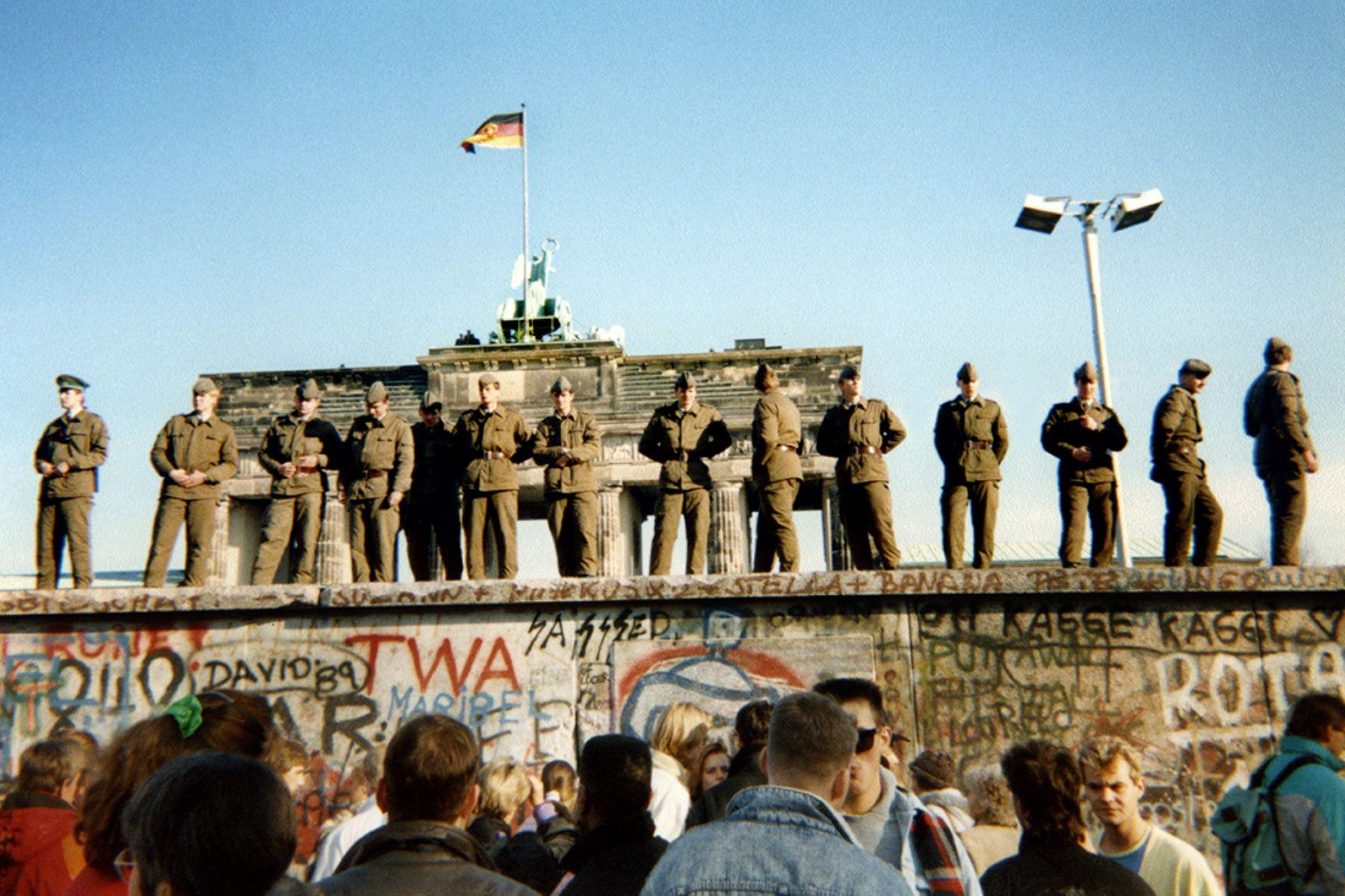 Los guardias fronterizos de Alemania del Este parados en una sección del Muro de Berlín frente a la Puerta de Brandeburgo  el 11 de noviembre de 1989. Foto: AFP