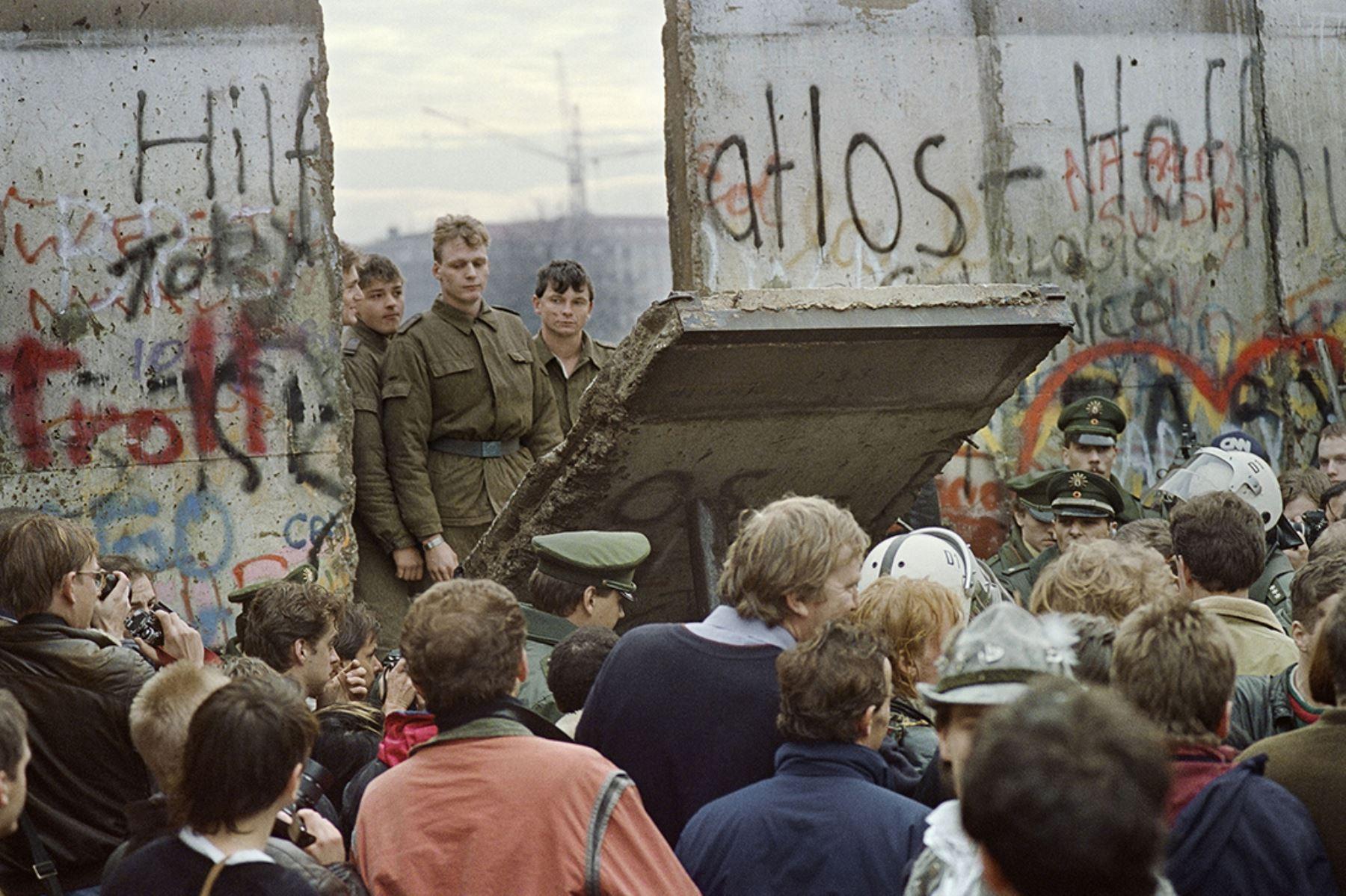 Los berlineses occidentales se agolpan frente al Muro de Berlín a principios del 11 de noviembre de 1989 mientras  los guardias fronterizos de Alemania Oriental ven caer parte del muro cerca a la Plaza Potsdamer. Dos días antes, Gunther Schabowski,  portavoz del Partido Comunista de la RDA , declaró que  los alemanes orientales serían libres de abandonar el país, sin permiso, en cualquier punto a lo largo de la frontera, incluidos los puntos de cruce a través del Muro en Berlín. Foto: AFP