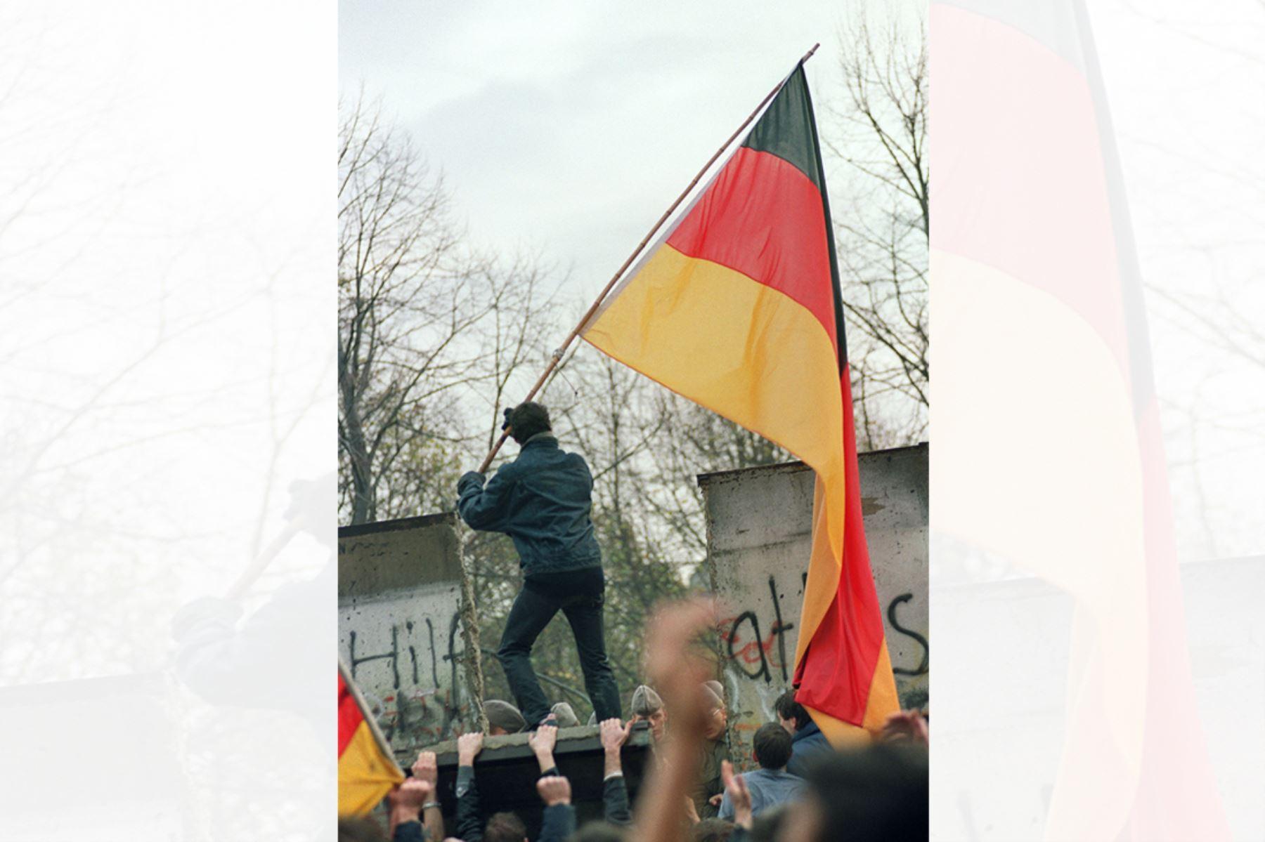 Un berlinés occidental se prepara para entregar una bandera de Alemania a los berlineses orientales a través de una parte del Muro de Berlín caído cerca de la Puerta de Brandenburgo el 11 de noviembre de 1989. Foto: AFP