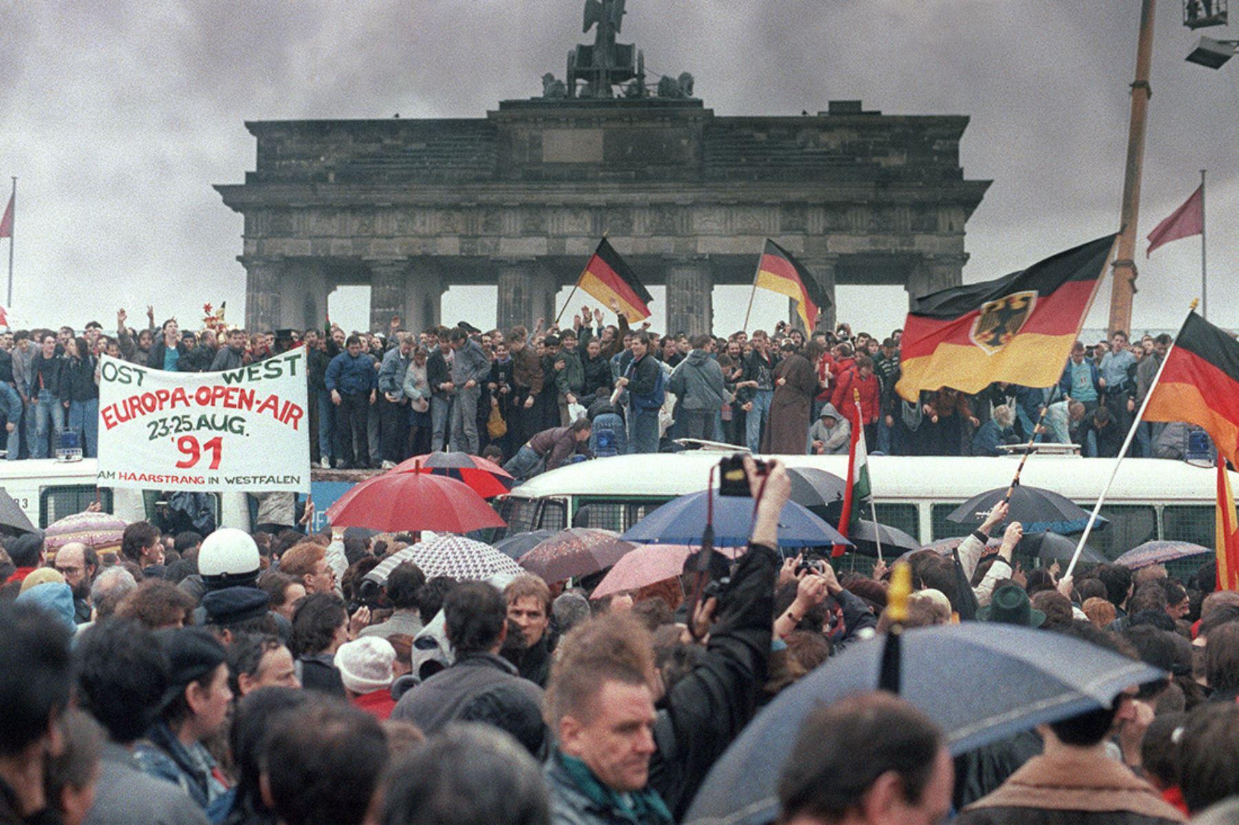 Ciudadanos de Alemania Oriental y Alemania Occidental se reúnen para celebrar a apertura de la Puerta de Brandenburgo en Berlín el 22 de diciembre de 1989. Foto: AFP