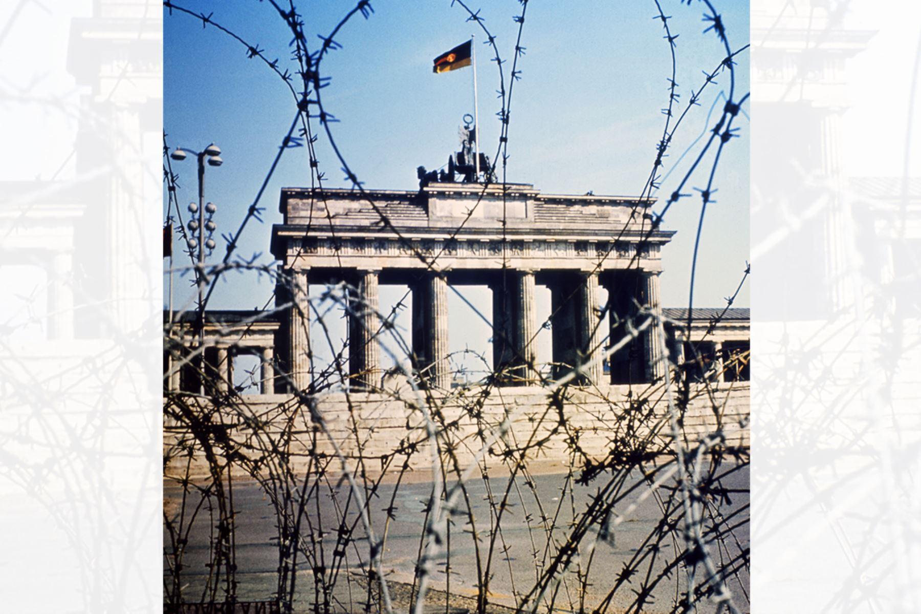 La Puerta de Brandenburgo se ve a través de una cerca de alambre de púas en junio de 1968.  Foto: AFP
