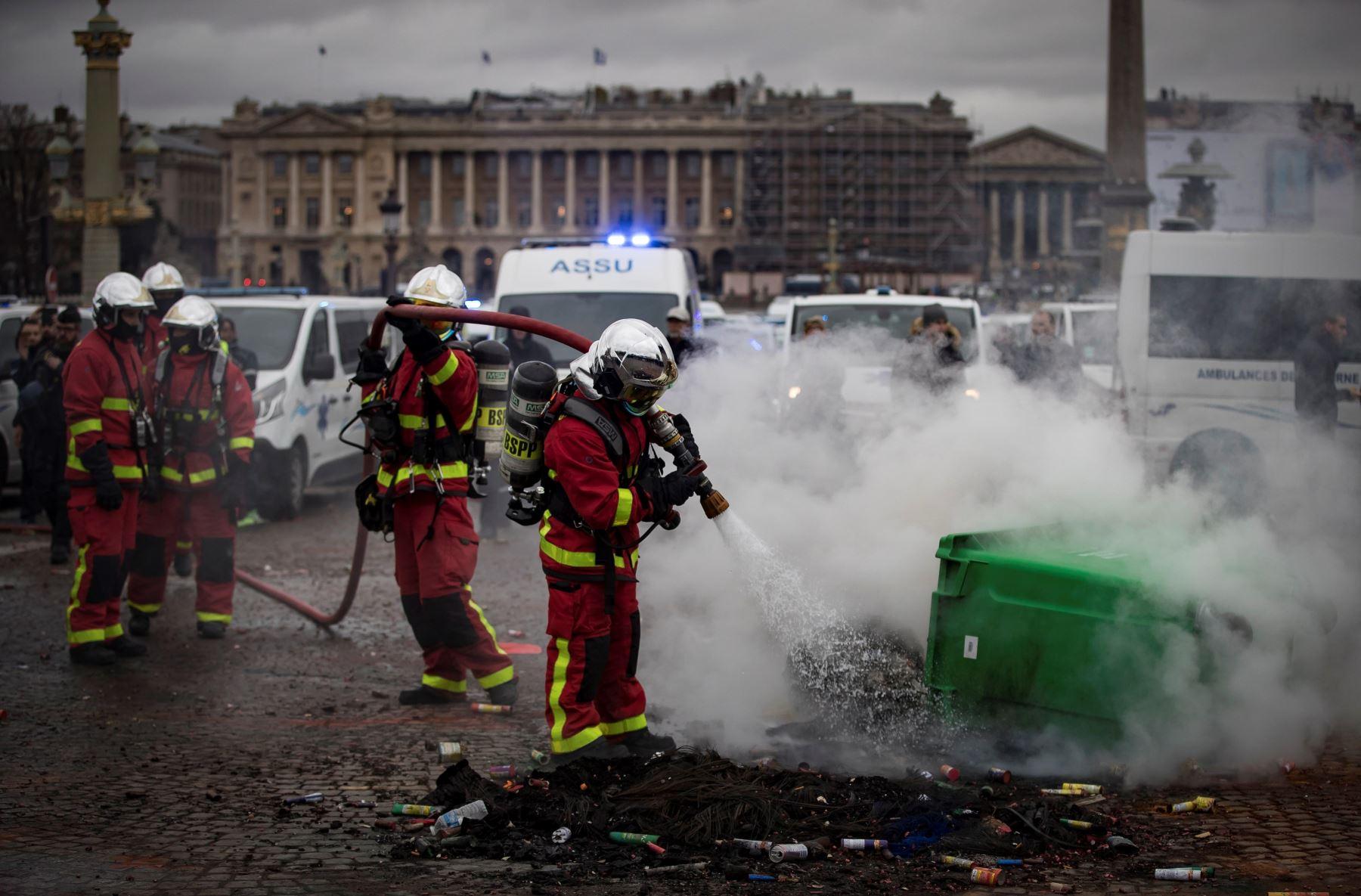 Bomberos apagan un fuego iniciado por conductores de ambulancias que participan en una protesta ante la Asamblea Nacional, en ParÌs, Francia. Los manifestantes bloquearon el tráfico junto a la Asamblea Nacional para exigir la suspensión de una reforma del sistema de financiación de los transportes sanitarios. EFE/