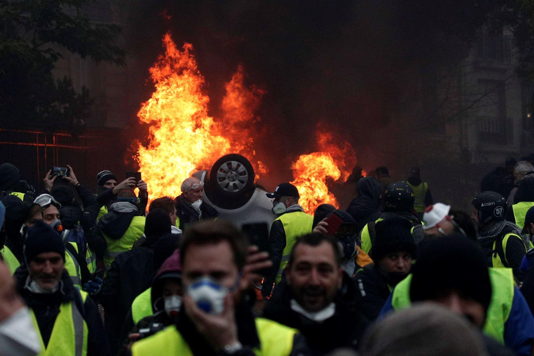 """Manifestantes con chalecos amarillos se enfrentan a la policía cerca del Arco del Triunfo de ParÌs, Francia. Las empresas francesas de transporte de mercancía en carretera (TRM, por sus siglas en francés) denunciaron hoy, 3 de diciembre de 2018, pérdidas de 400 millones de euros debido a los bloqueos de camiones del movimiento de los """"chalecos que amarillos"""" desde hace casi tres semanas. EFE"""