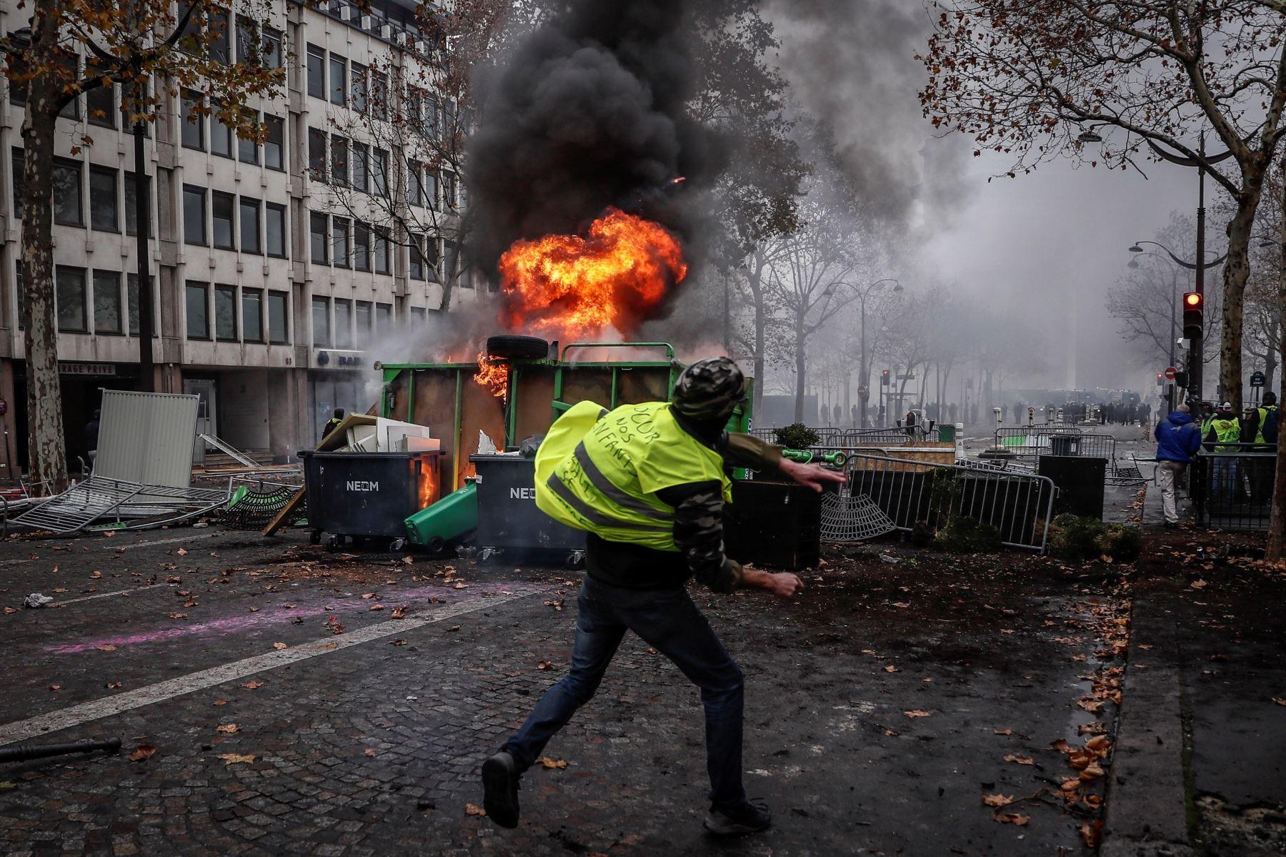 """Un manifestante de los autodenominados """"chalecos amarillos"""" se enfrenta a los agentes junto a una barricada en llamas Foto: EFE"""