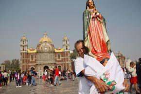 Un hombre carga una imagen de la virgen de Guadalupe, en los exteriores de la Basílica Foto: EFE