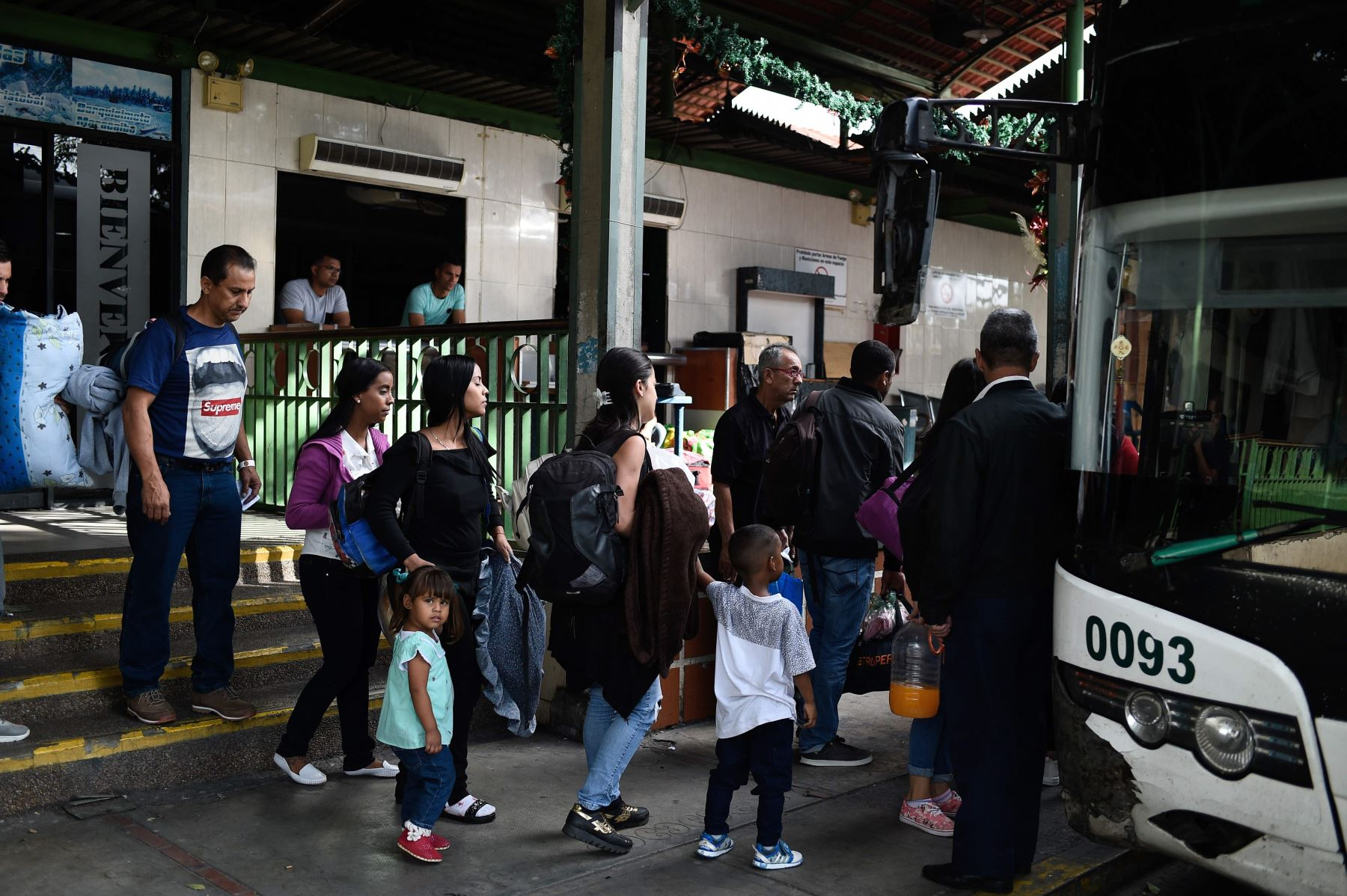 La gente hace cola para abordar un autobús en una estación en Caracas Foto: AFP