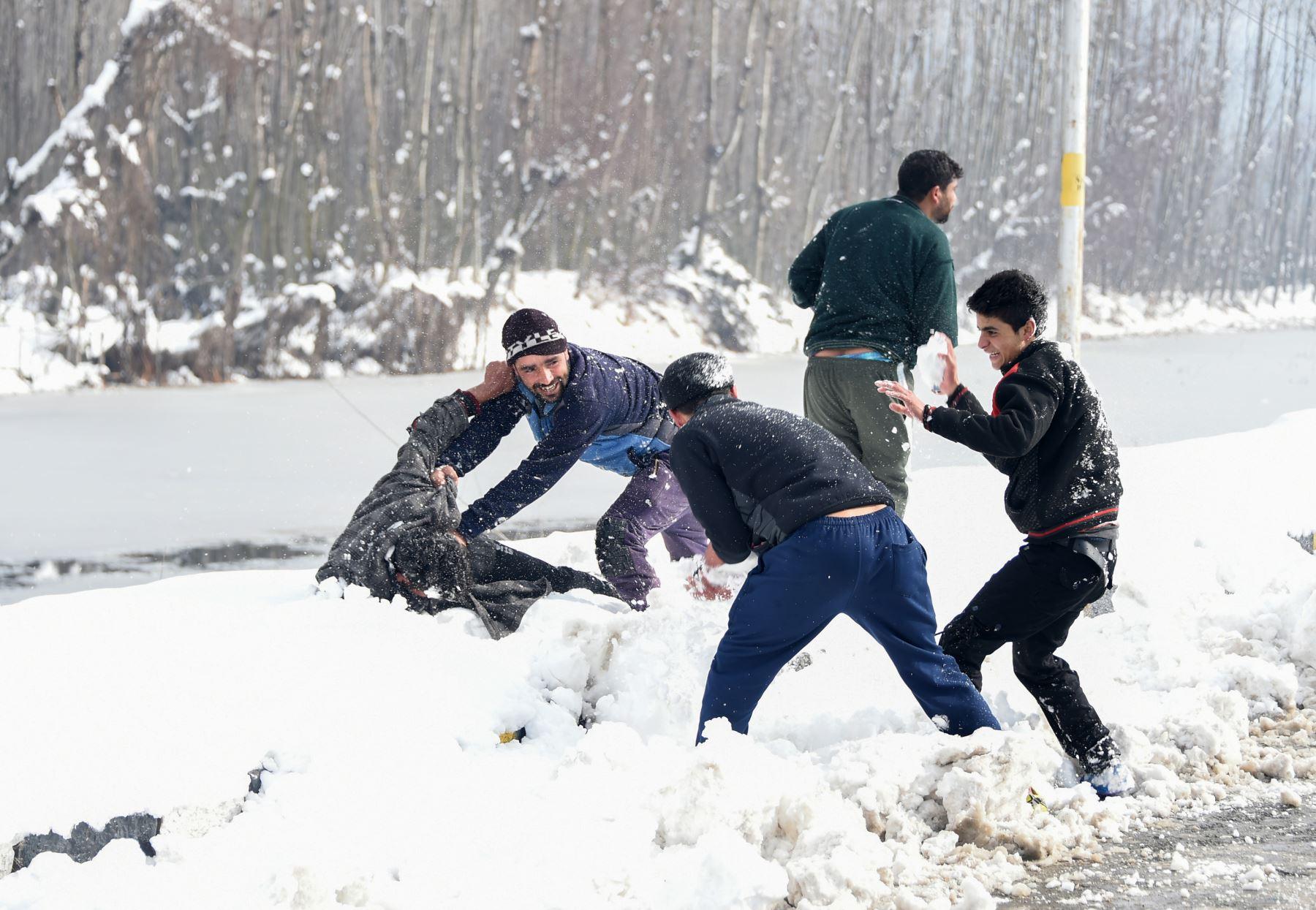 Los jóvenes de Cachemira juegan con nieve en las orillas del lago Dal después de la nevada en Srinagar.  AFP