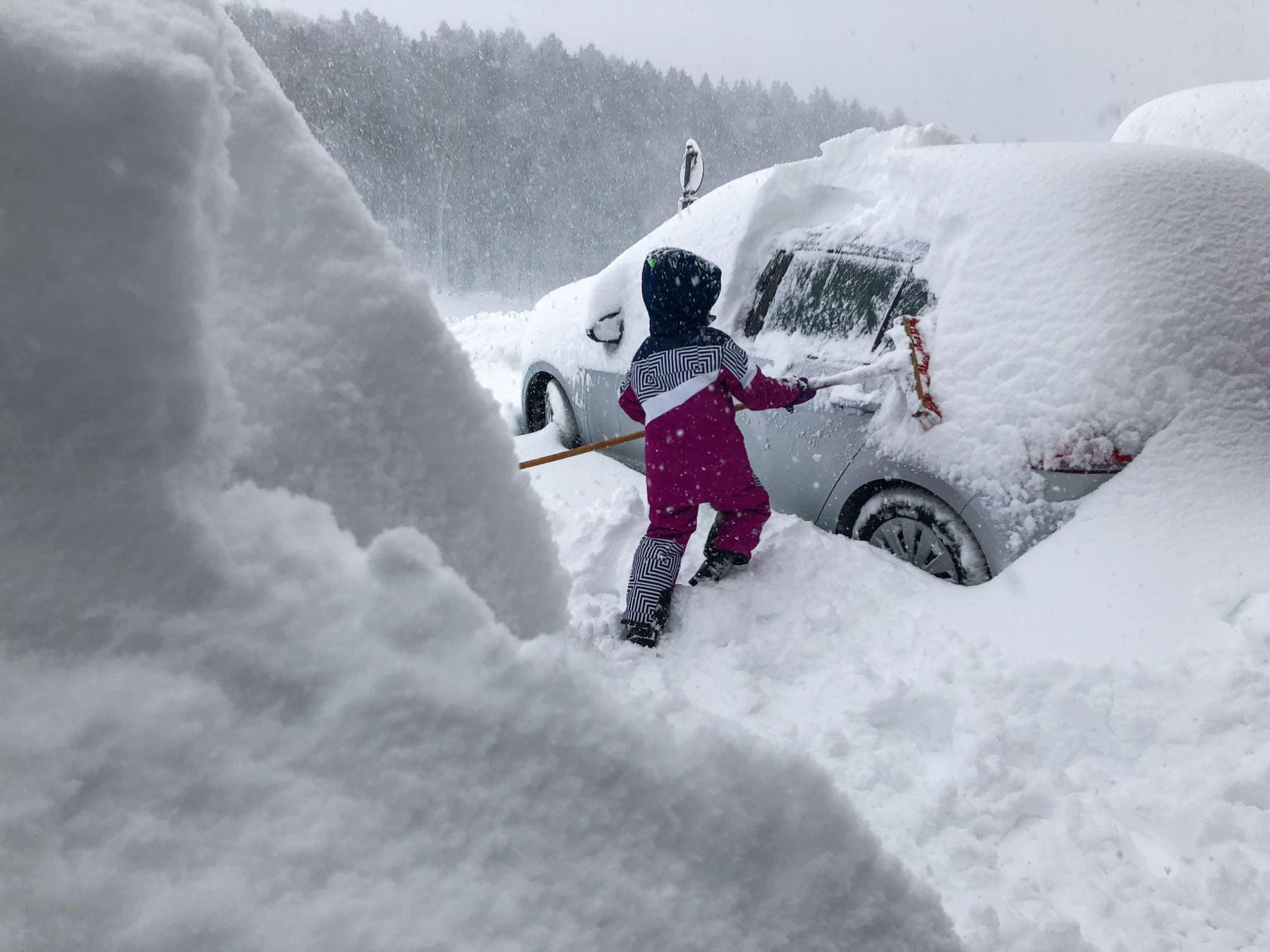 Un niño limpia una ventanilla de nieve de un automóvil en Salzburgo, Austria, mientras cae nueva nieve. AFP