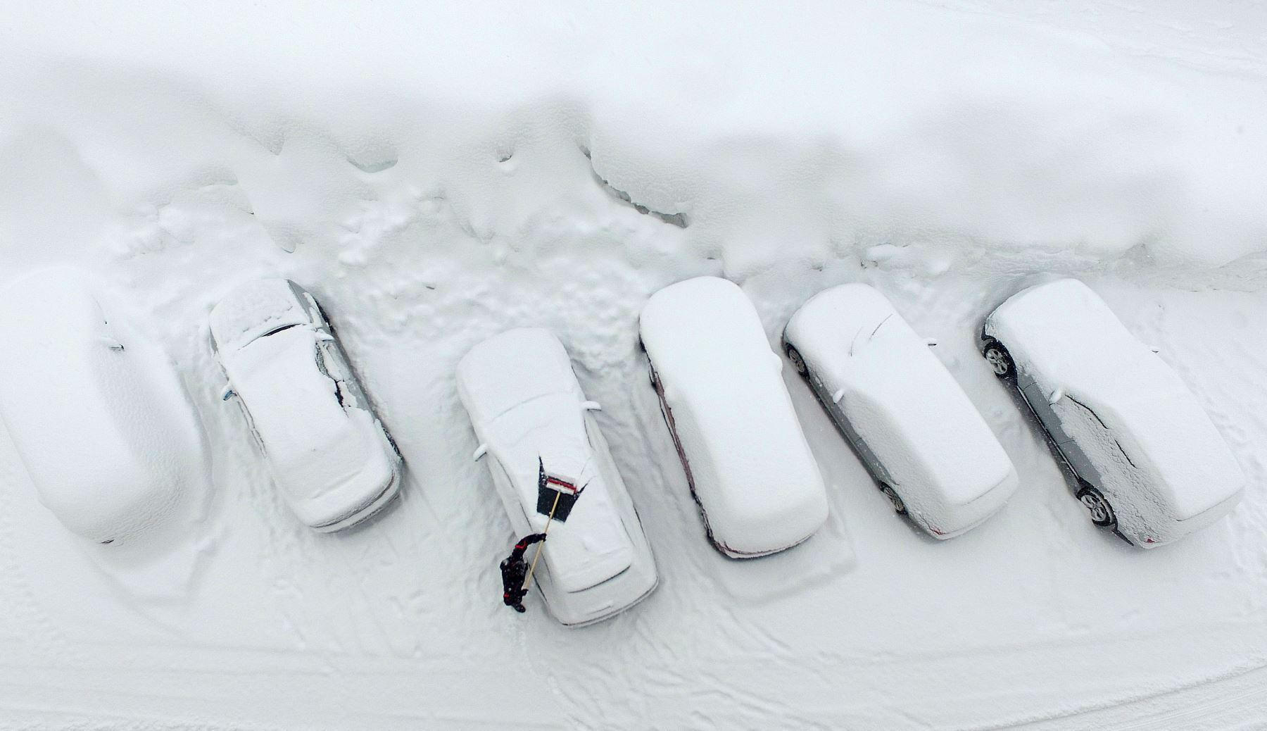 Una fotografía aérea muestra a un hombre limpiando su automóvil de la nieve después de fuertes nevadas en Ramsau am Dachstein, Austria. AFP