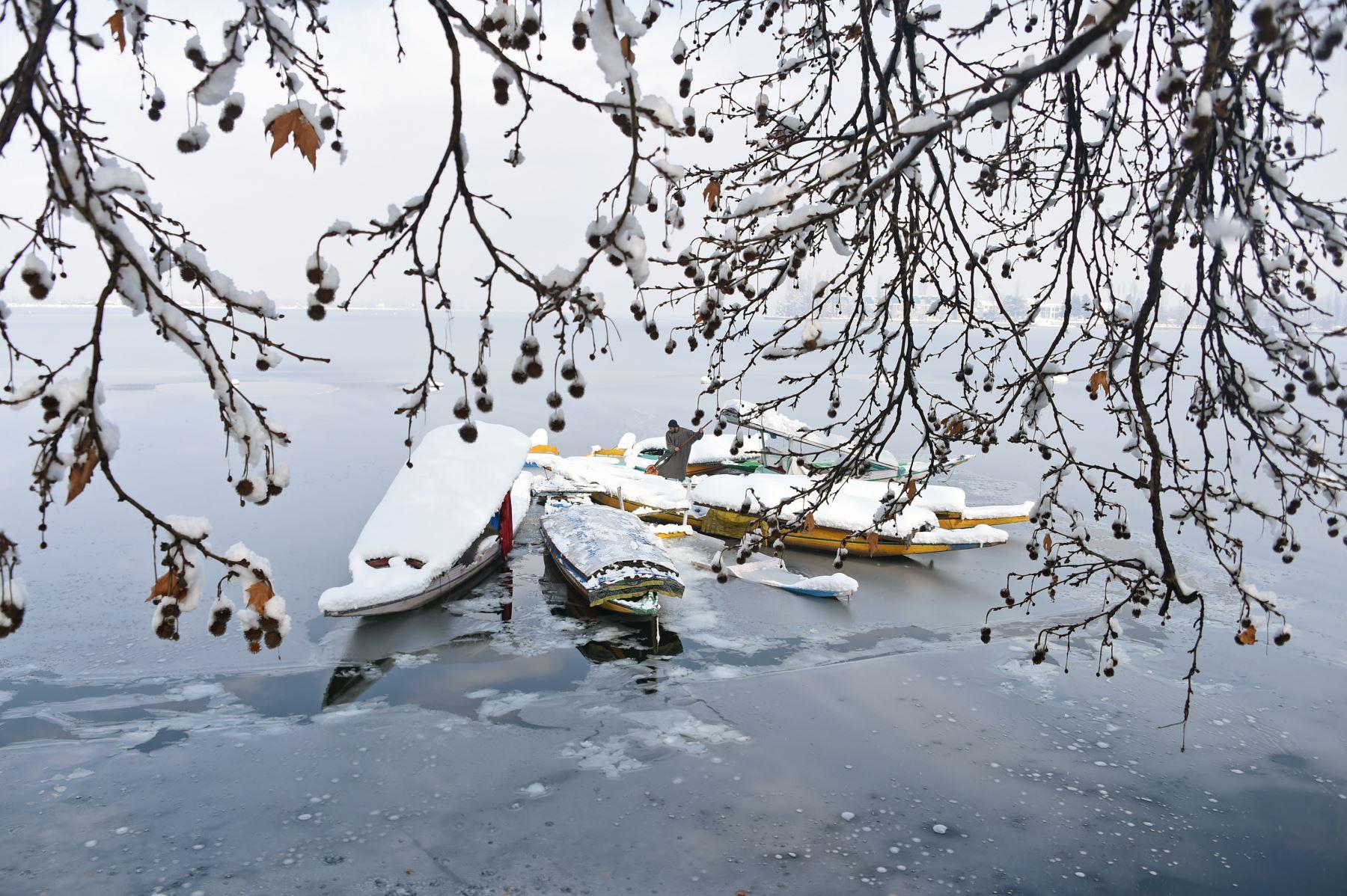 Después de una nevada en Srinagar, un botero de Cachemira quita la nieve de los botes de shikara cerca de una porción congelada del Lago Dal. - Los enlaces de la carretera de Cachemira con el resto de la India se cortaron cuando la fuerte nevada cerró la carretera nacional Jammu-Srinagar. AFP