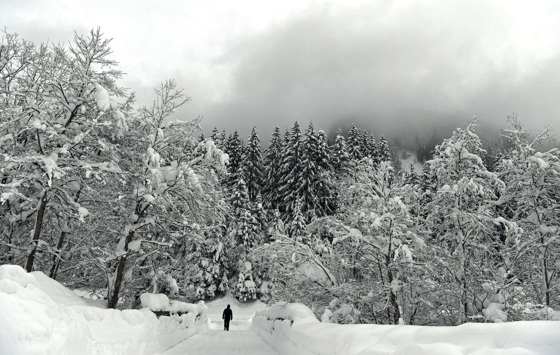 Un hombre solitario camina en un paisaje cubierto de nieve  cerca de Obertauern, Austria, donde cayeron enormes cantidades de nieve durante el inicio del mont. AFP