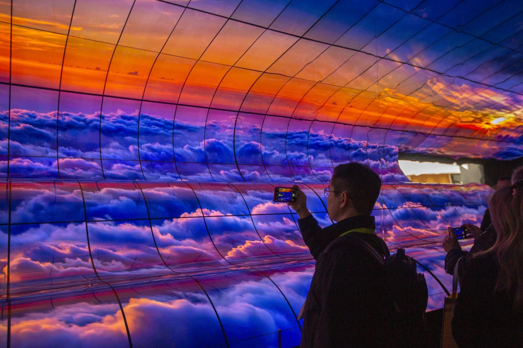 La gente toma fotos de teléfonos inteligentes de un gran panel de televisores LG OLED curvos en la exhibición de LG durante el CES 2019 en Las Vegas. AFP