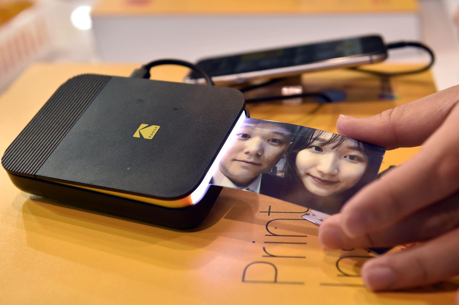 Un asistente saca una fotografía de una impresora instantánea Kodak en el stand de Kodak durante el CES 2019. AFP
