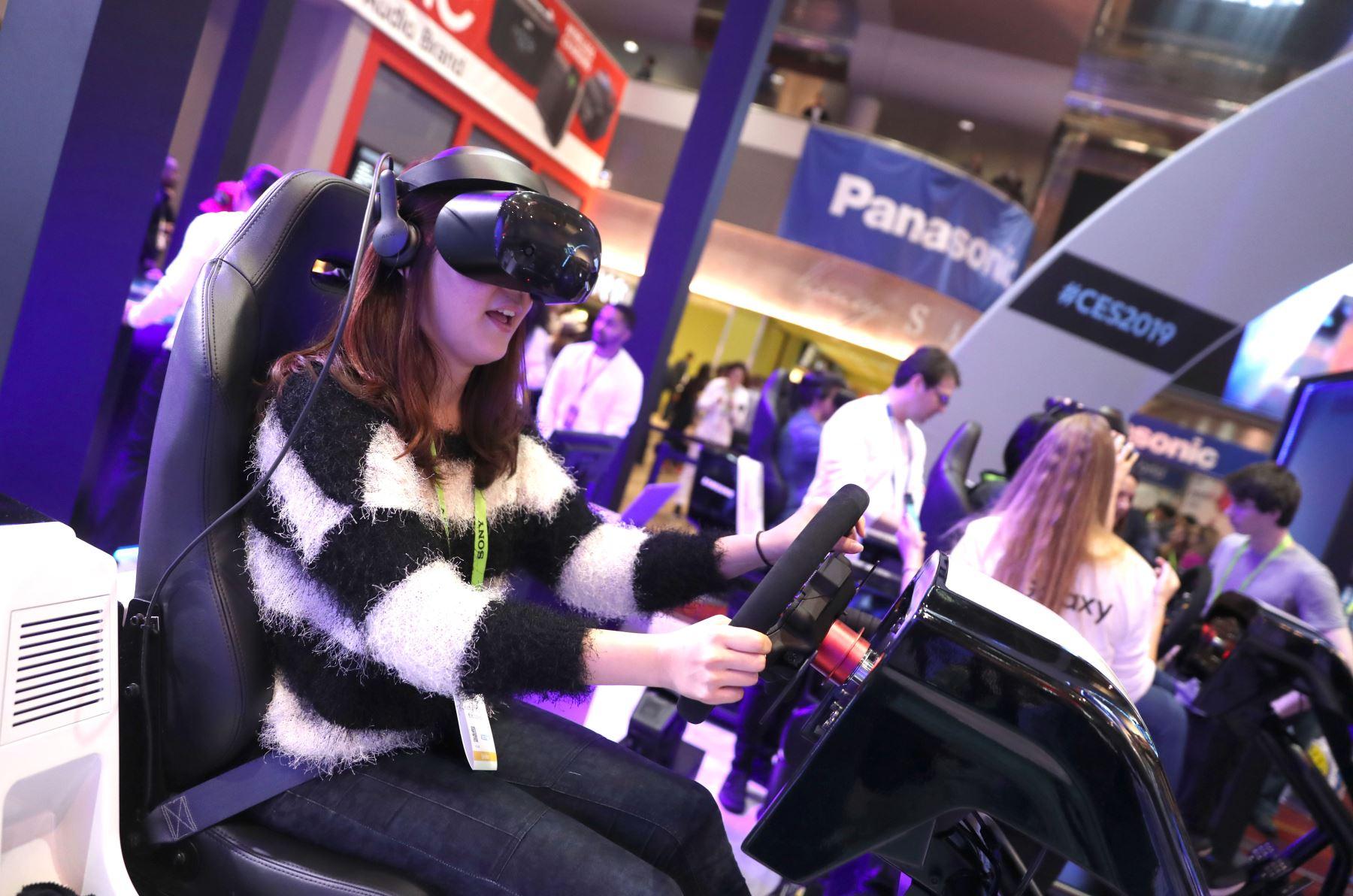 Un asistente juega un juego de carreras de realidad virtual en el stand de Samsung Galaxy Experience Zone durante el CES 2019. AFP