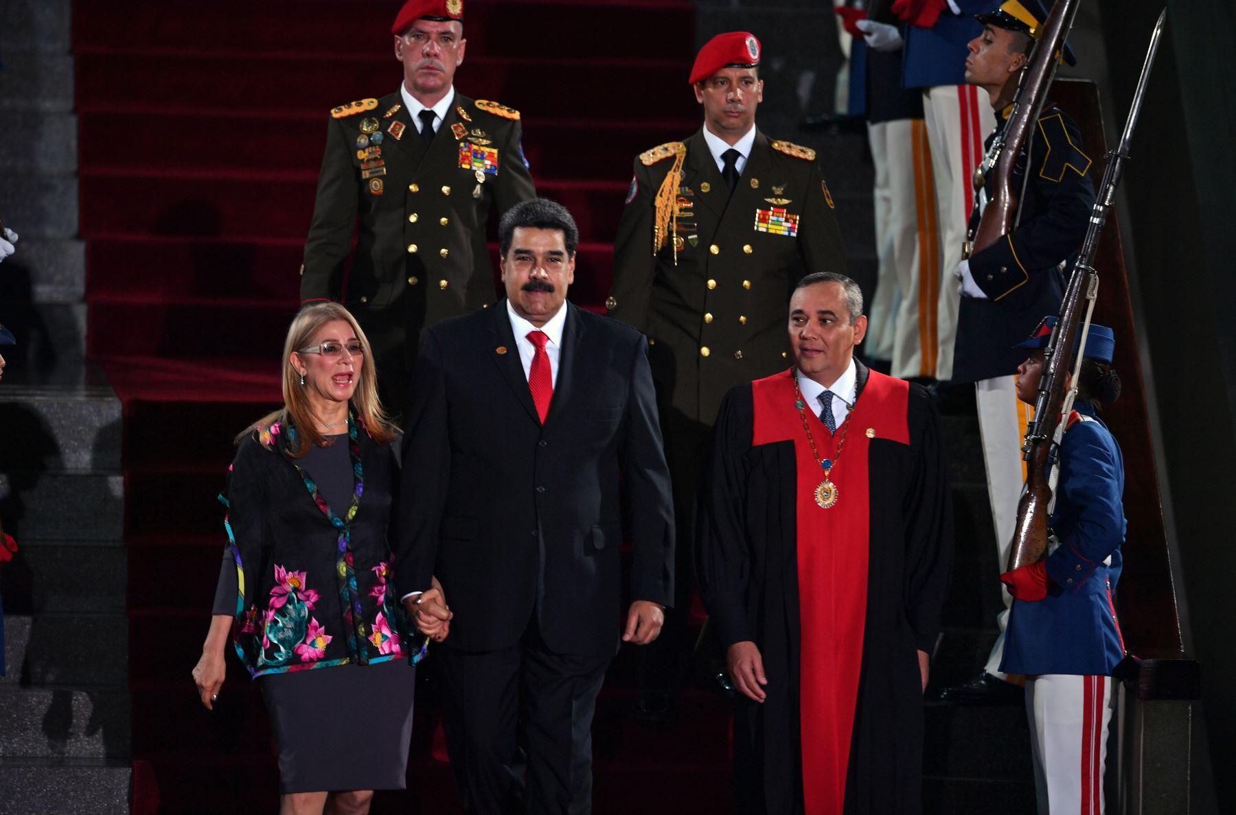 El presidente de Venezuela, Nicolás Maduro (C) camina flanqueado por la Primera Dama Cilia Flores y el presidente de la Corte Suprema de Justicia (TSJ), Maikel Moreno (R), al llegar a la ceremonia de inauguración de su segundo mandato, en la sede del TSJ en Caracas.  Maduro comienza un nuevo término que los críticos consideran ilegítimo, con la economía en caída libre y el país más aislado que nunca.. AFP