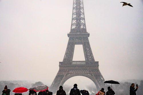 La gente se queda mirando la Torre Eiffel mientras caen nevadas en la capital francesa Foto: AFP