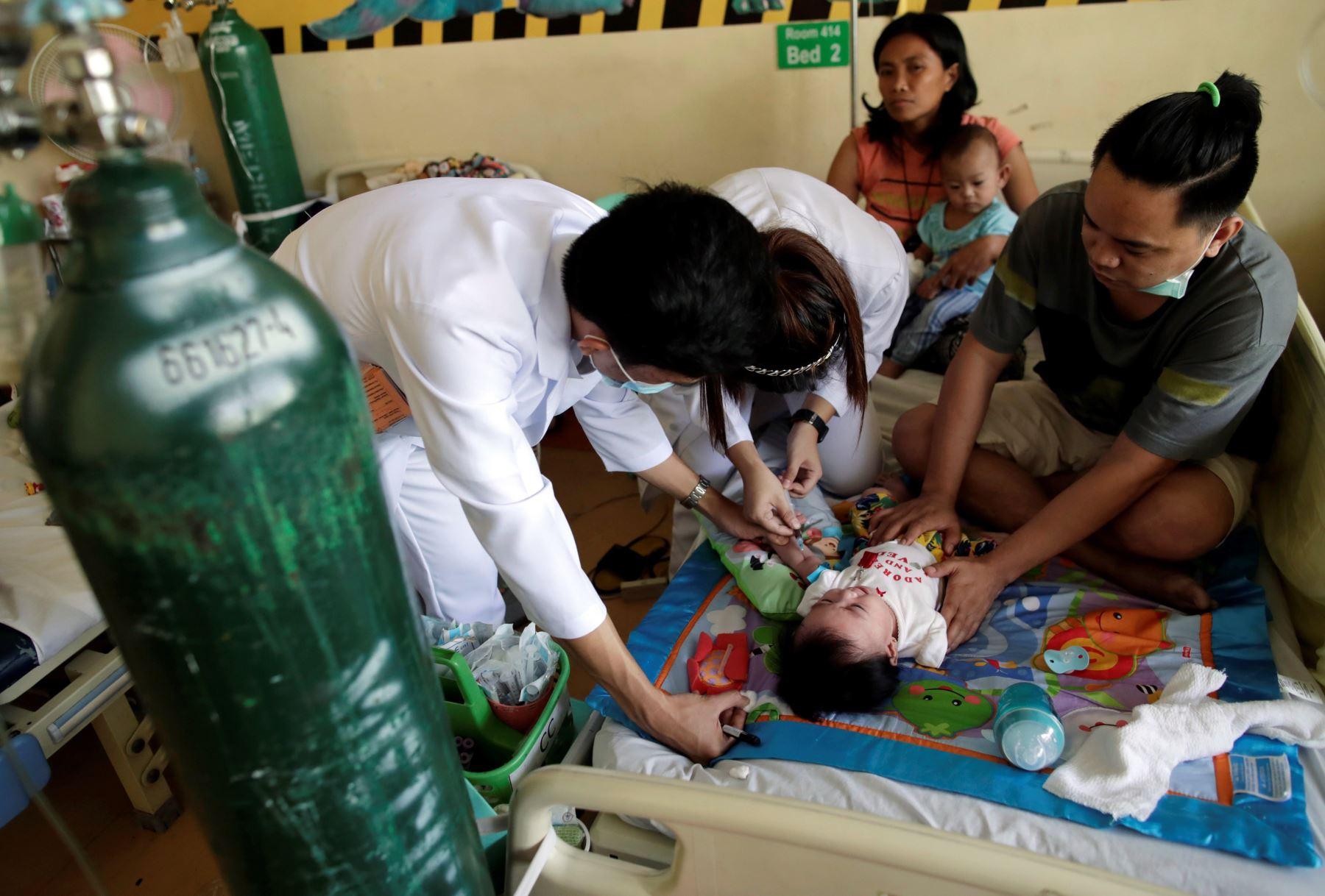Doctores filipinos atienden a un niño enfermo de sarampión, este jueves, en Manila, Filipinas. Foto: EFE
