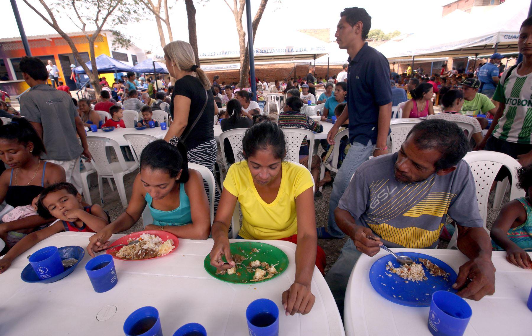 Ciudadanos venezolanos comen tras recibir una ración de comida en el comedor Divina Providencia, en Cúcuta (Colombia). EFE