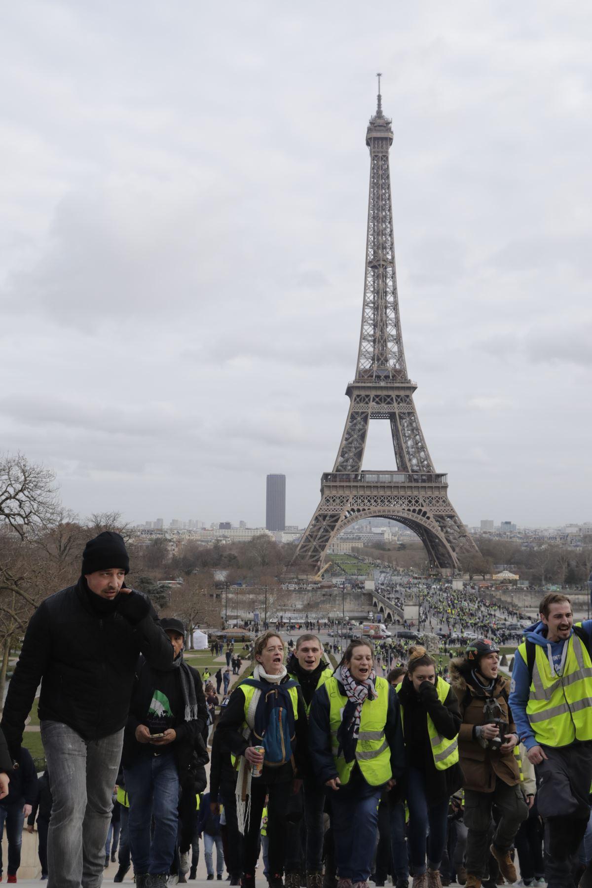 Los manifestantes de chalecos amarillos marchan en París frente a la Torre Eiffel  durante el 13º sábado consecutivo de manifestaciones. El movimiento