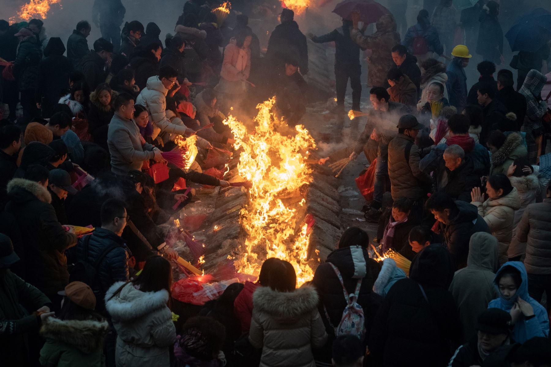 Los fieles chinos ofrecen oraciones y queman incienso en el quinto día del Año Nuevo Lunar en el Templo Budista Guiyuan en Wuhan, provincia de Hubei, centro de China,  ya que China celebra el Año del Cerdo con una semana de vacaciones en el Festival de Primavera. , el festival más importante del año. Miles de fieles chinos queman incienso y otras ofrendas al Dios de la Riqueza en el quinto día del Año Nuevo Lunar en el Templo Guiyuan, en Wuhan, en el centro de China. AFP
