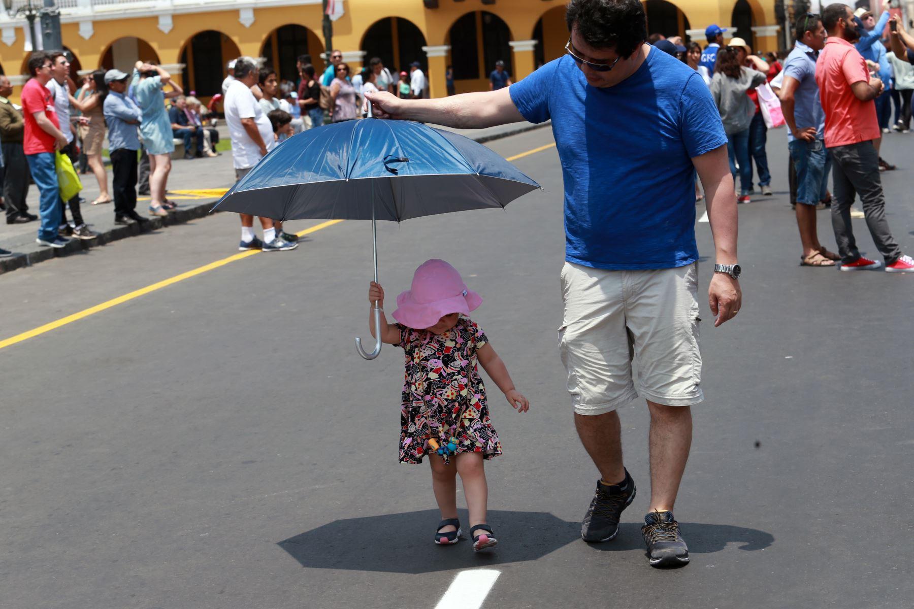 Una pequeña niña es protegida del sol por su padre mientras pasean por la Plaza Mayor de Lima. Foto: ANDINA/Norman Córdova