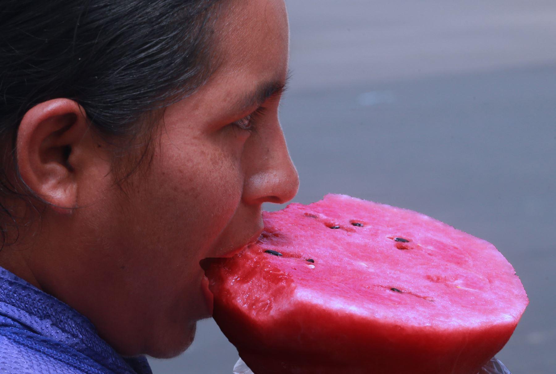 Una persona come un trozo de sandia para refrescarse del calor. Foto: ANDINA/Norman Córdova