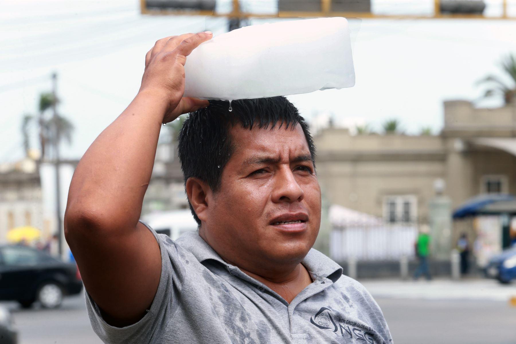 Un hombre camina con un trozo de hielo en la cabeza por las calles de Lima. Foto: ANDINA/Norman Córdova